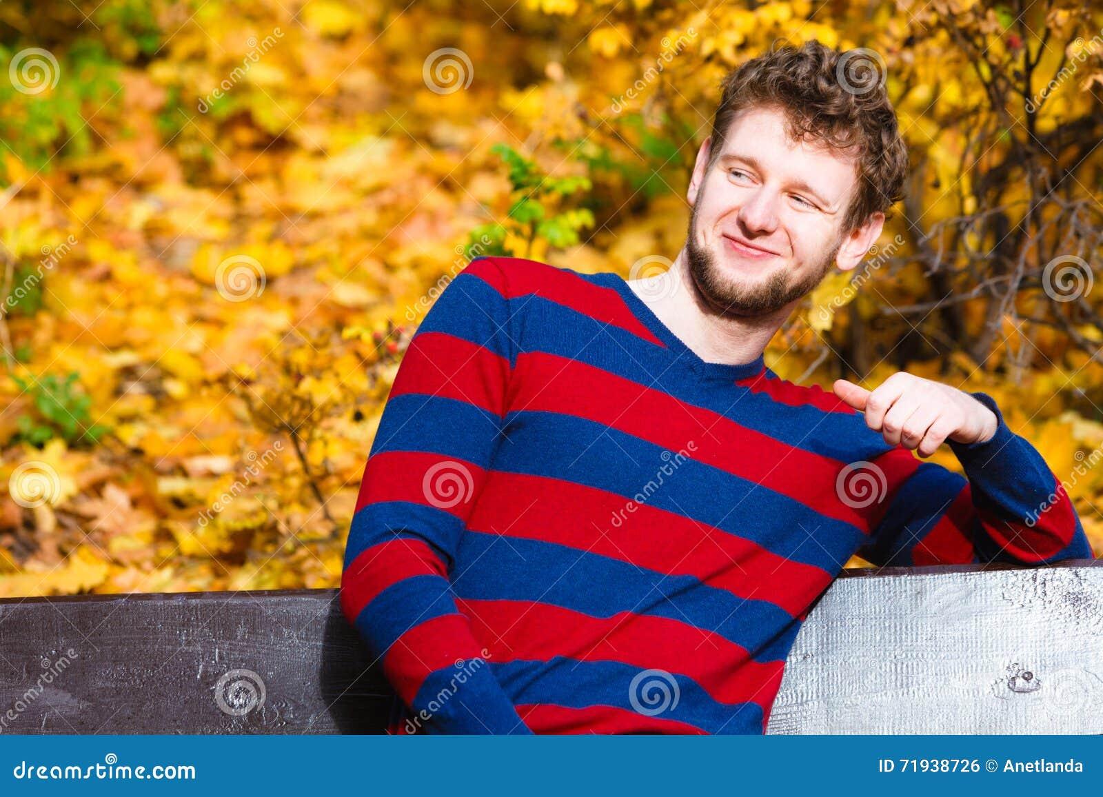 Человек сидя на стенде в парке