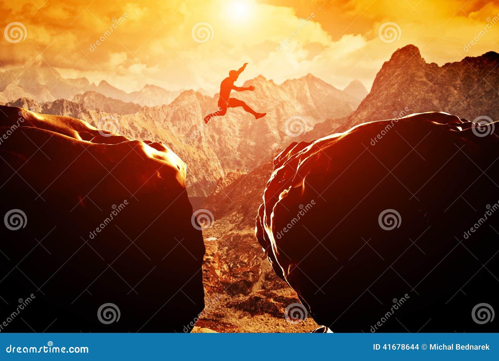 Человек скача над пропастью между 2 горами