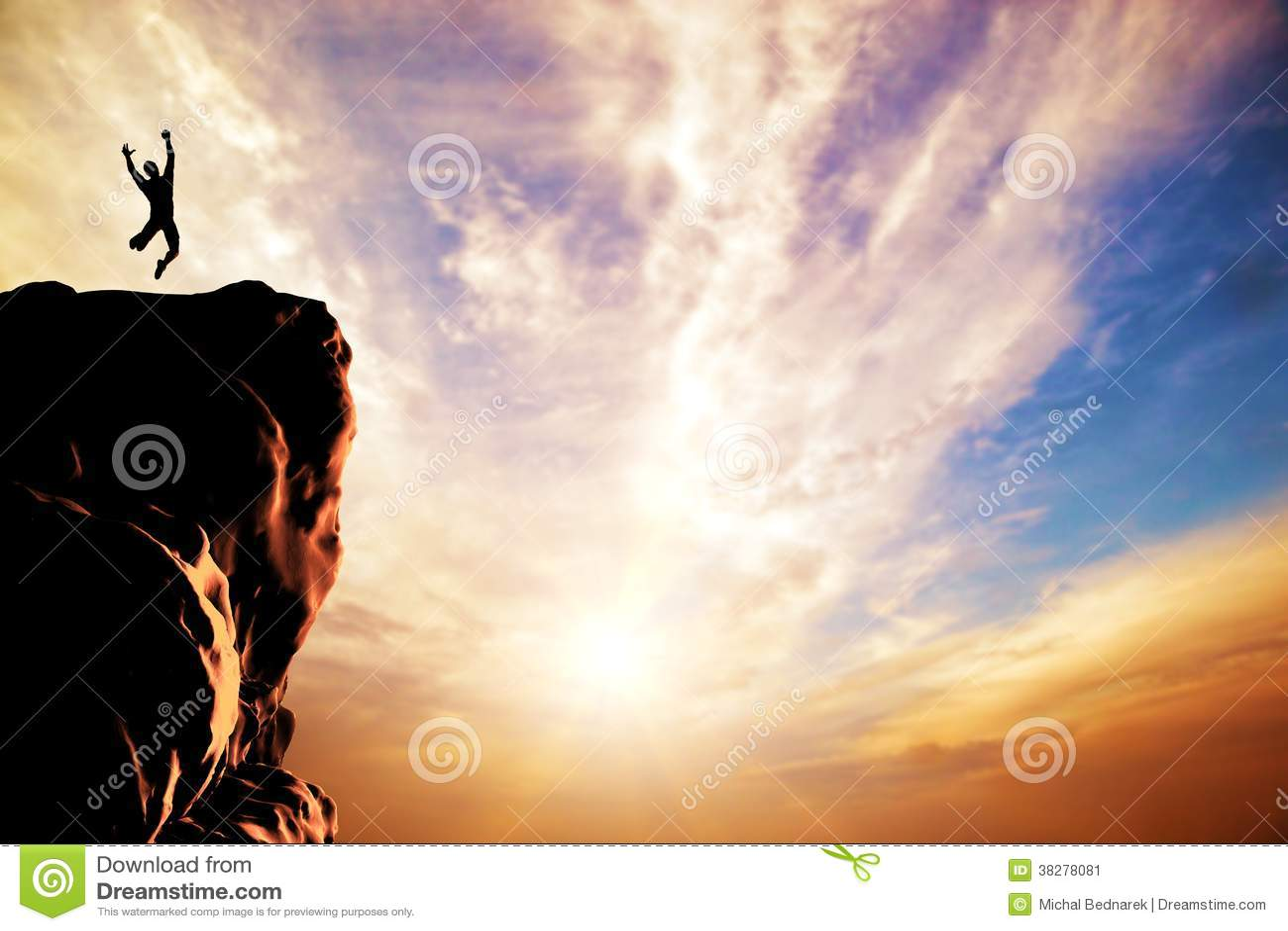 Человек скача для утехи на пике горы