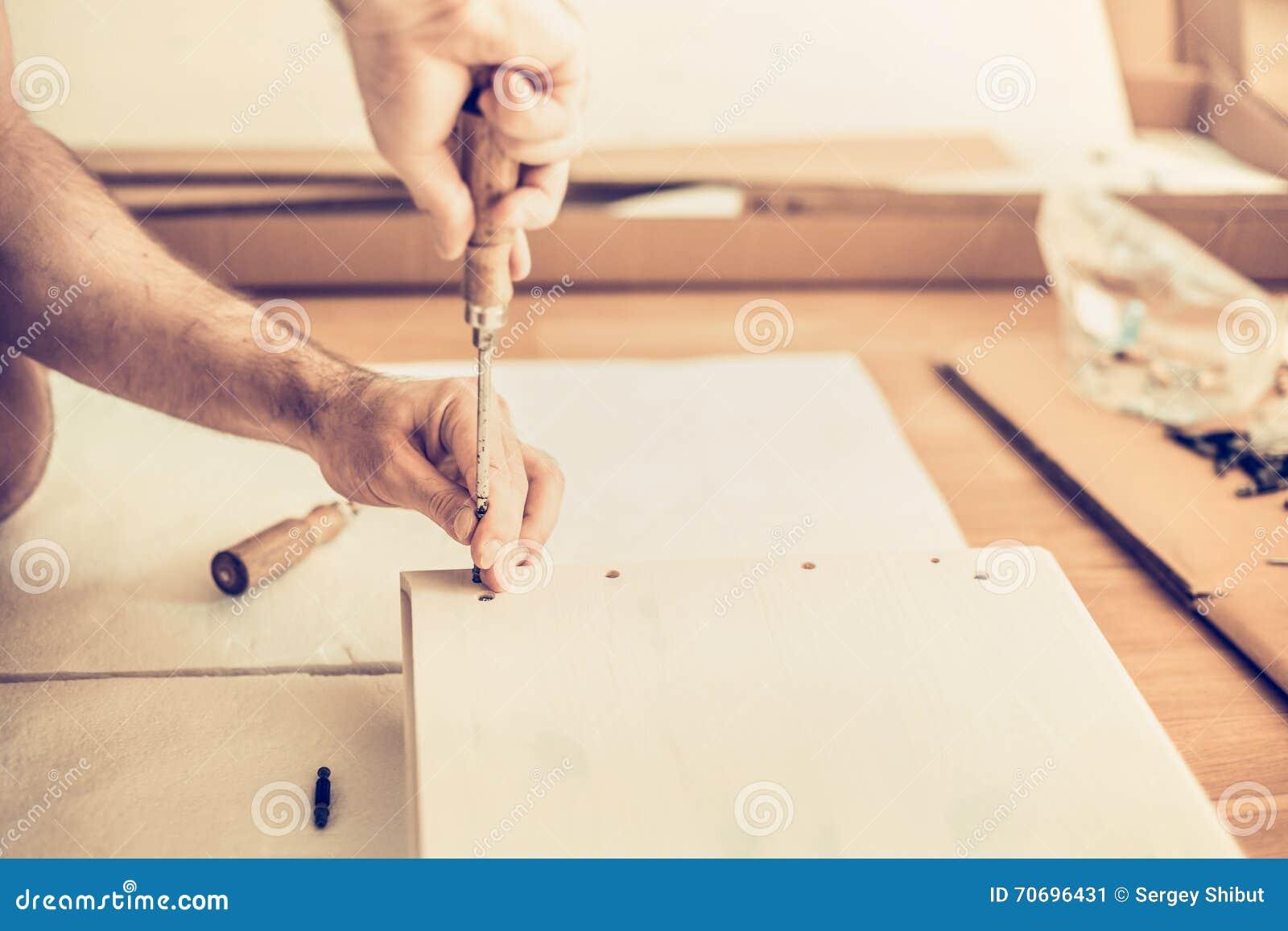 Человек собирает шкаф, переплетает винты шлицы, собрание мебели