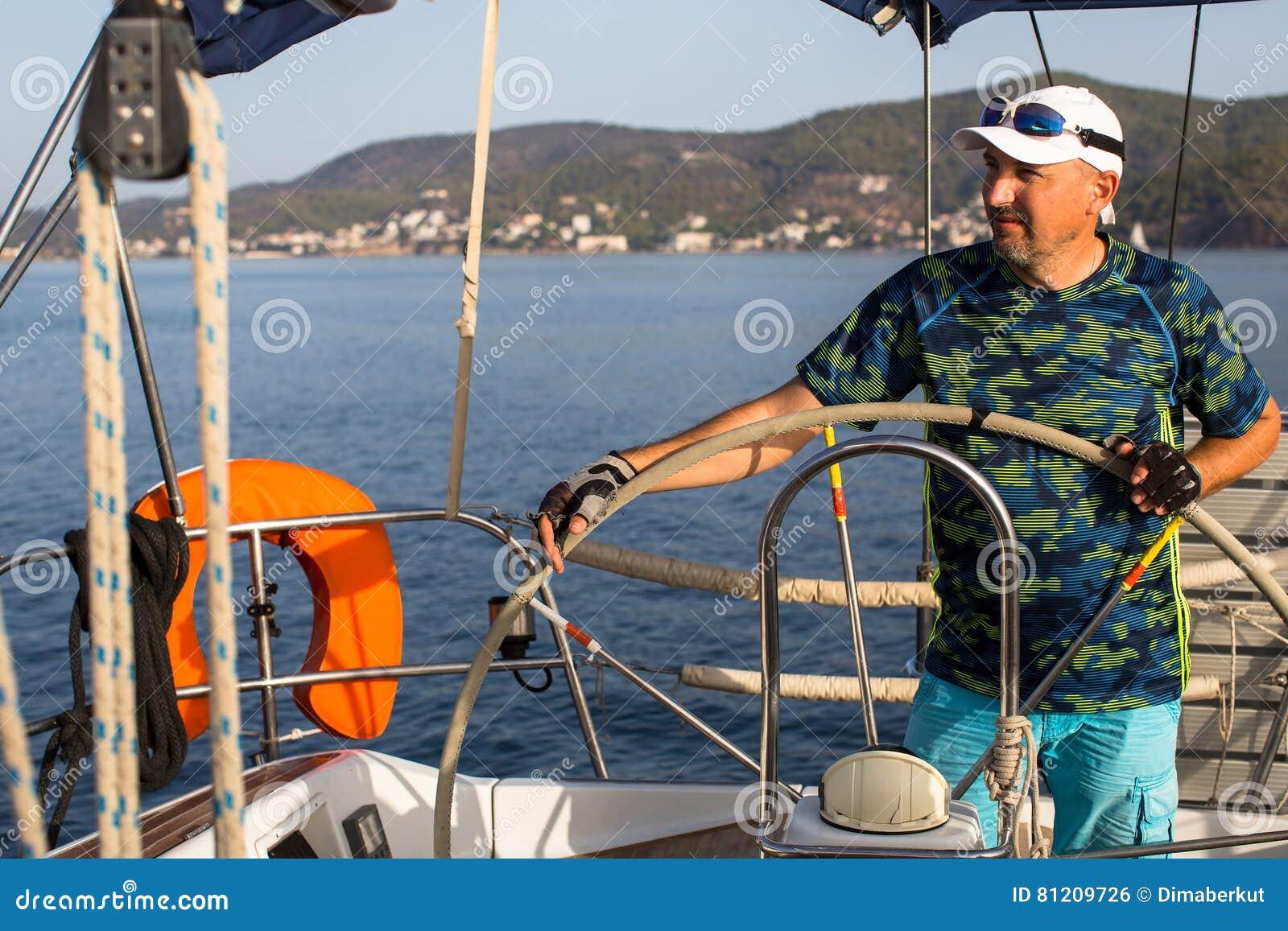 Человек стоит на кормиле и приводится в действие сосуд плавания Спорт