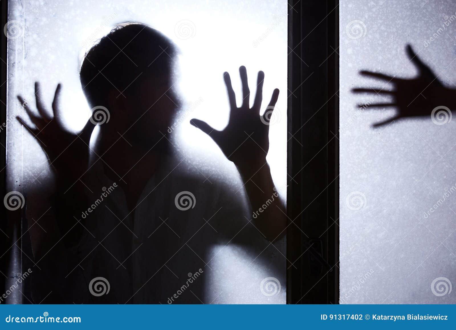 Человек стоя за стеклянной дверью
