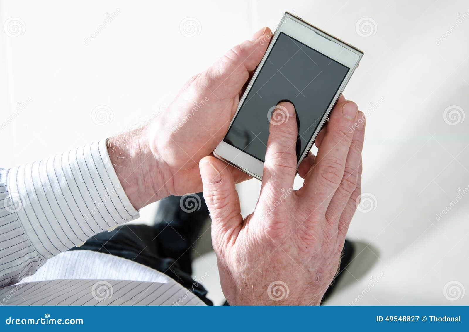 Человек стоя используя smartphone