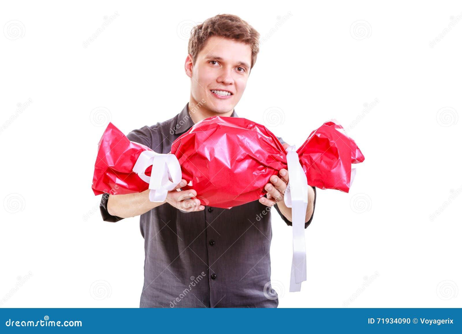 Человек с большой красной конфетой