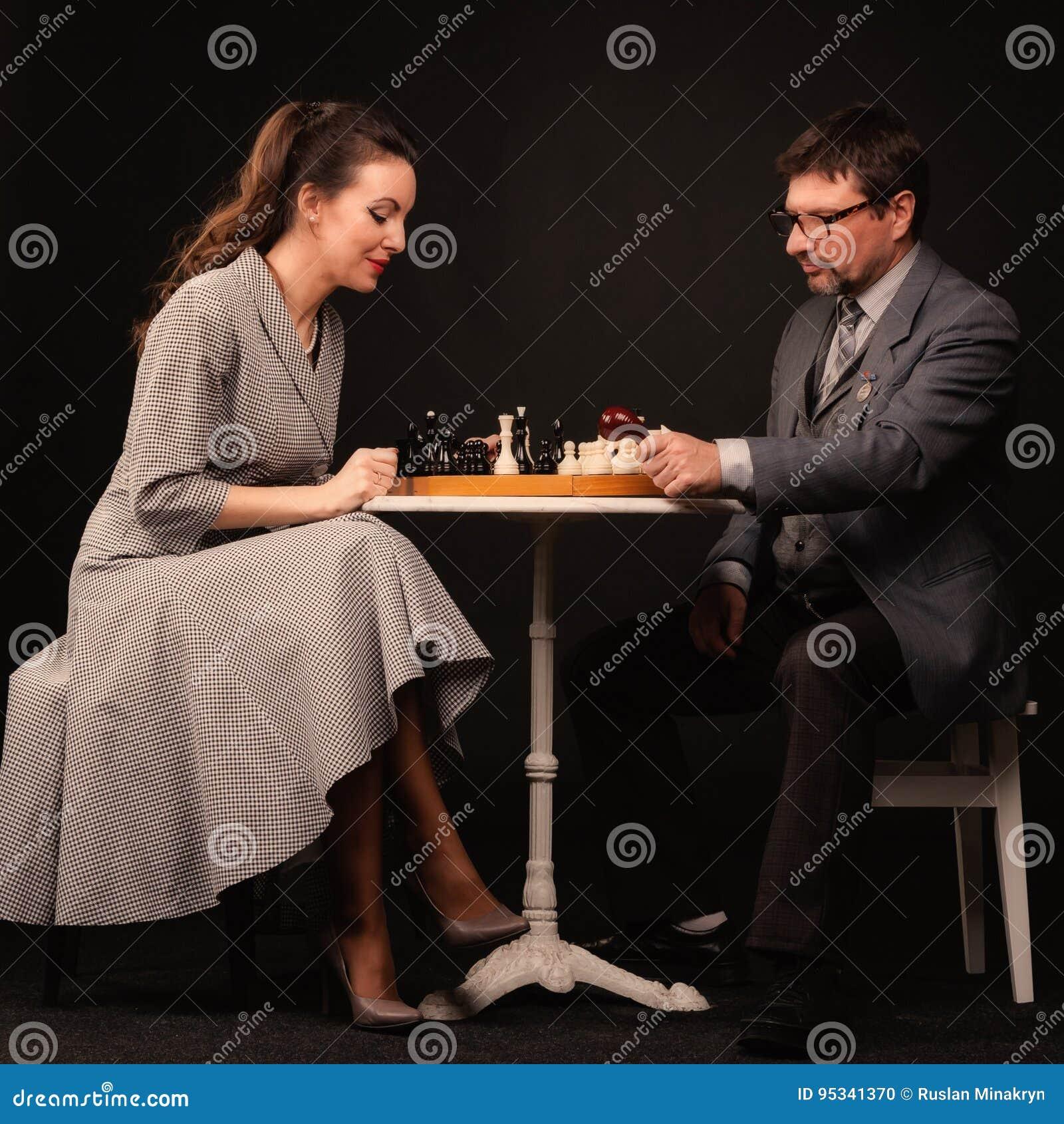 Человек с девушкой играет шахмат и курит трубу на темном backgr