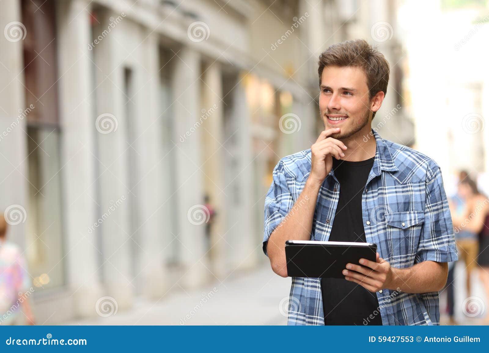 Человек с таблеткой думая в улице