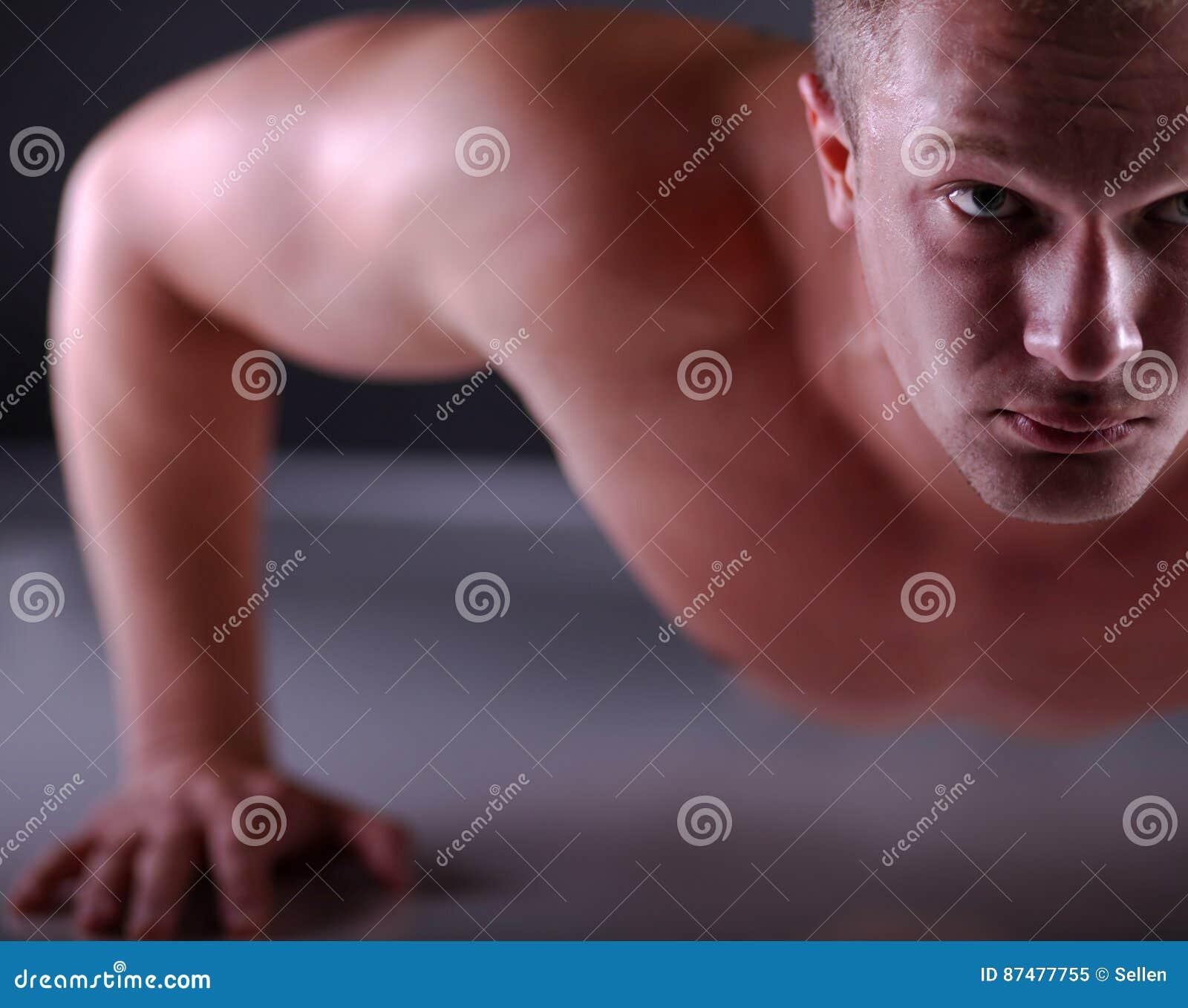 Человек фитнеса делать нажимает поднимает на поле, серой предпосылке