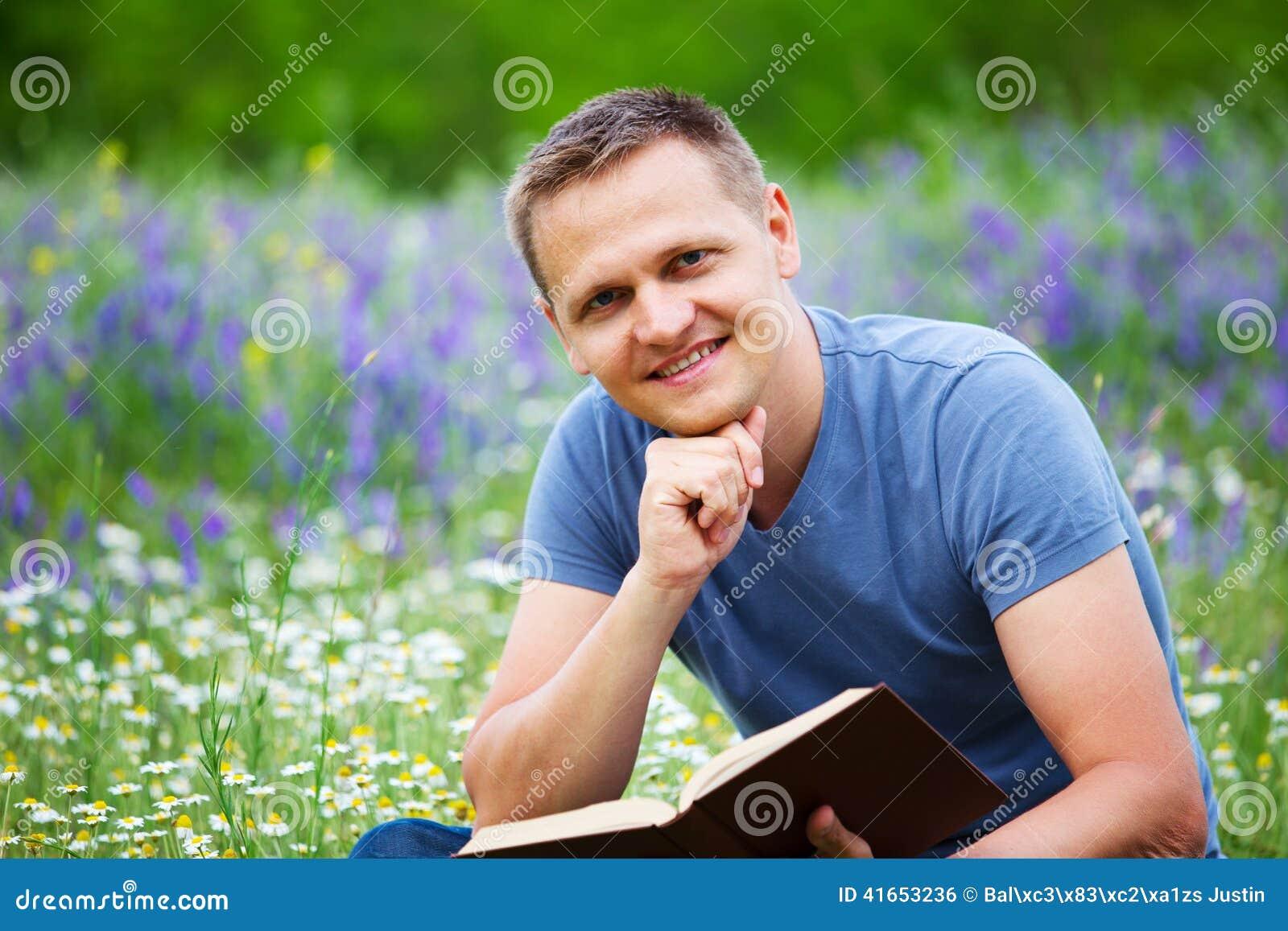 Человек читает книгу в поле