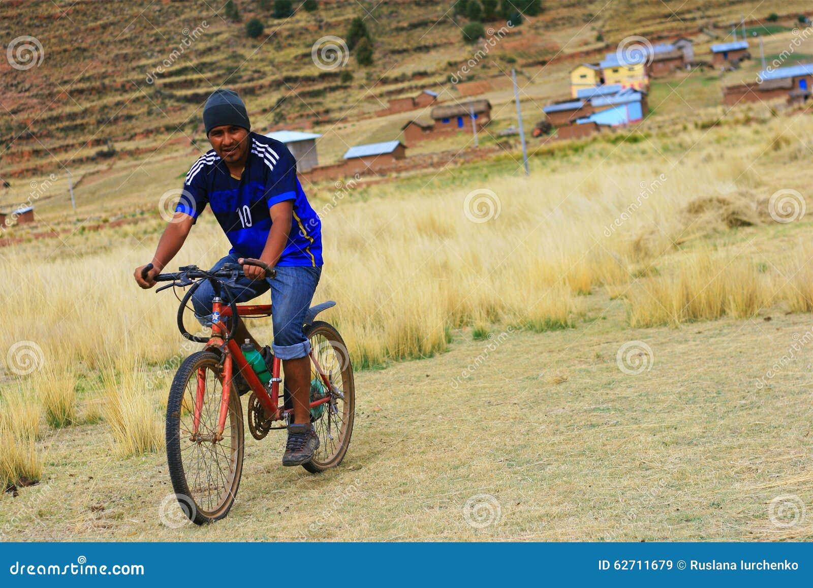 Человек Aymara ехать велосипед