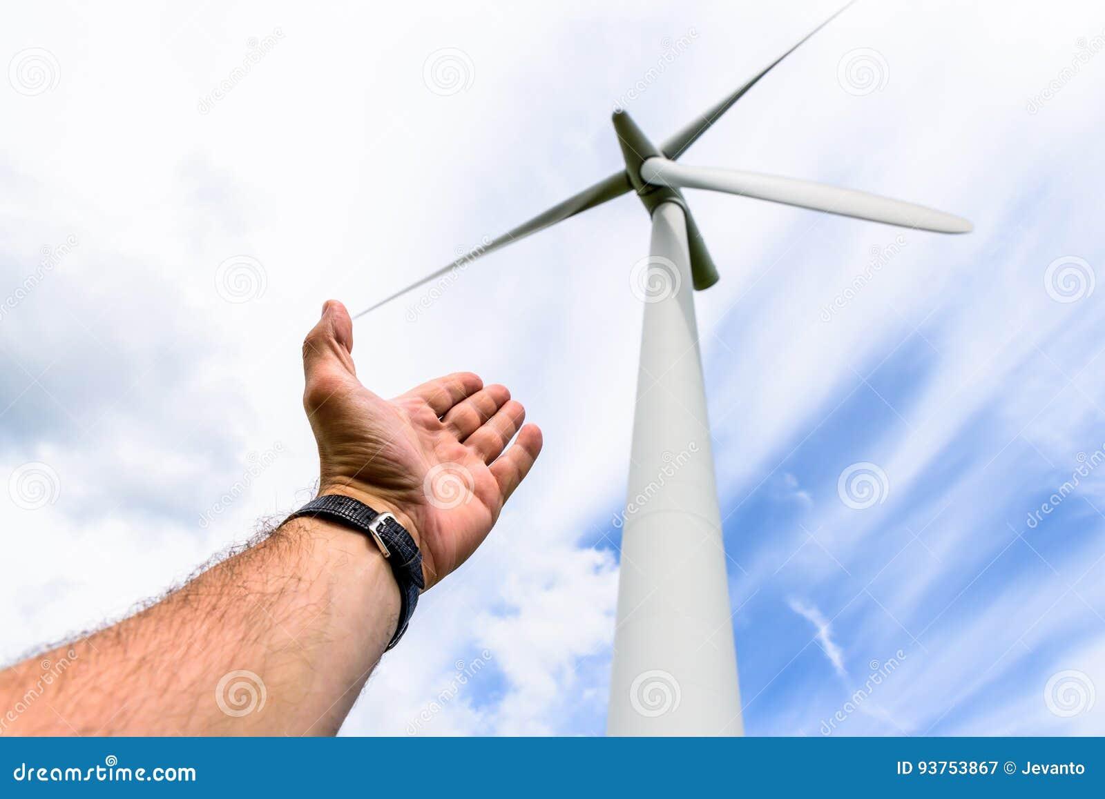 Человеческая рука направляя к турбинам энергии ветра производит электричество