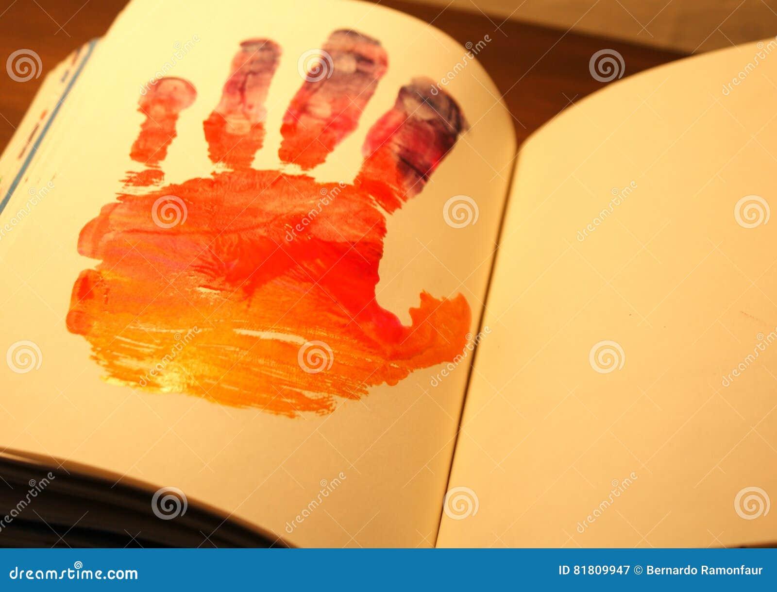 Человеческая рука покрашенная на тетради