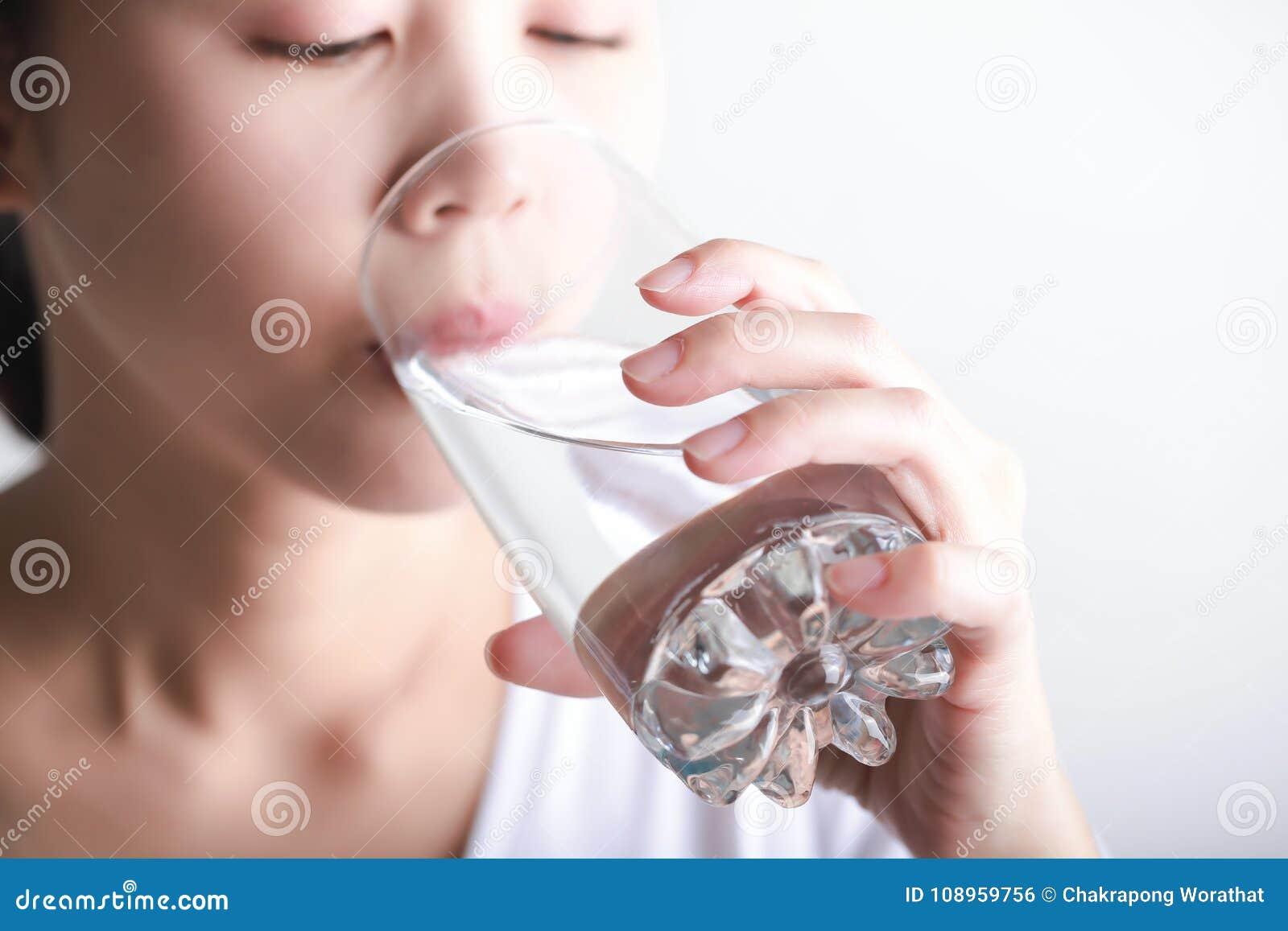 Чистая вода молодой женщины выпивая в ее руке