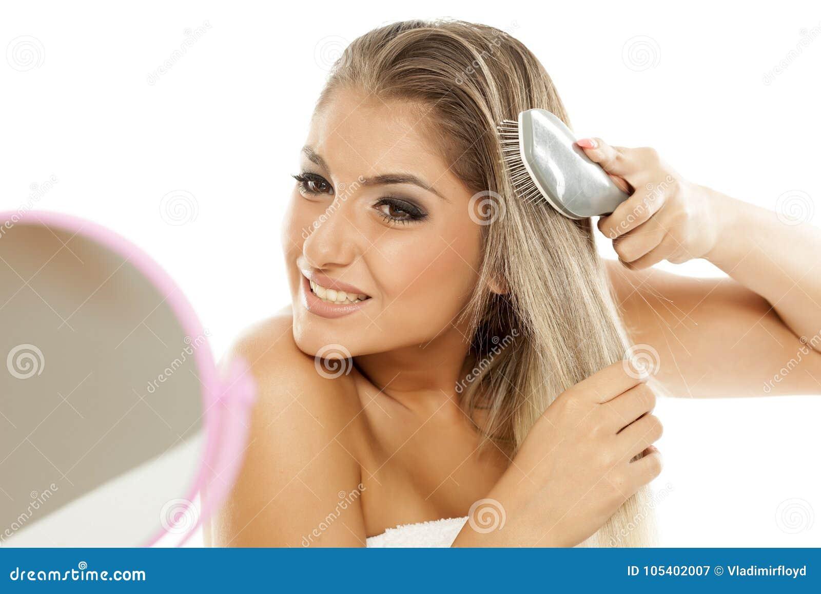 чистя щеткой волосы ее женщина