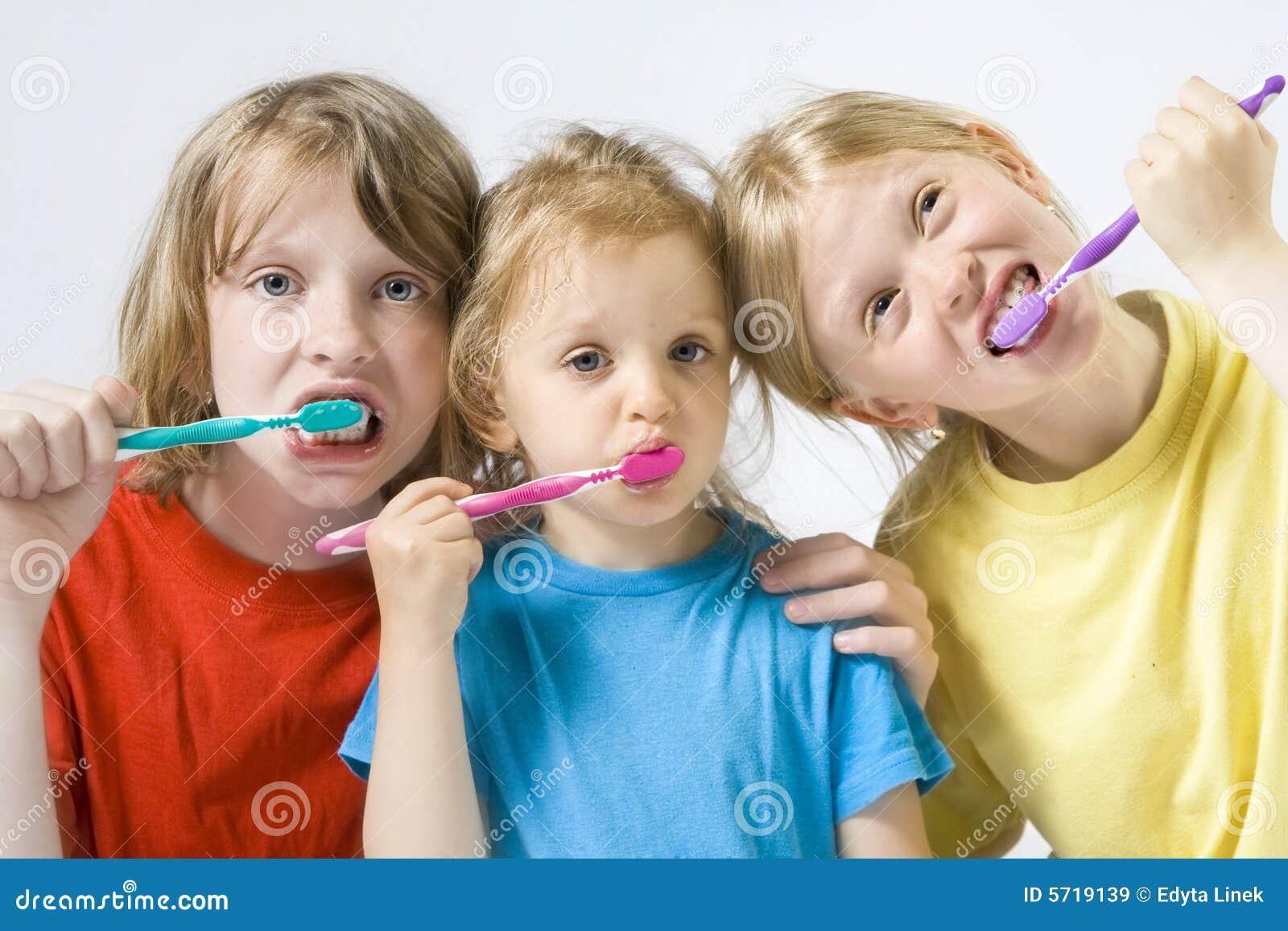 чистя щеткой зубы детей