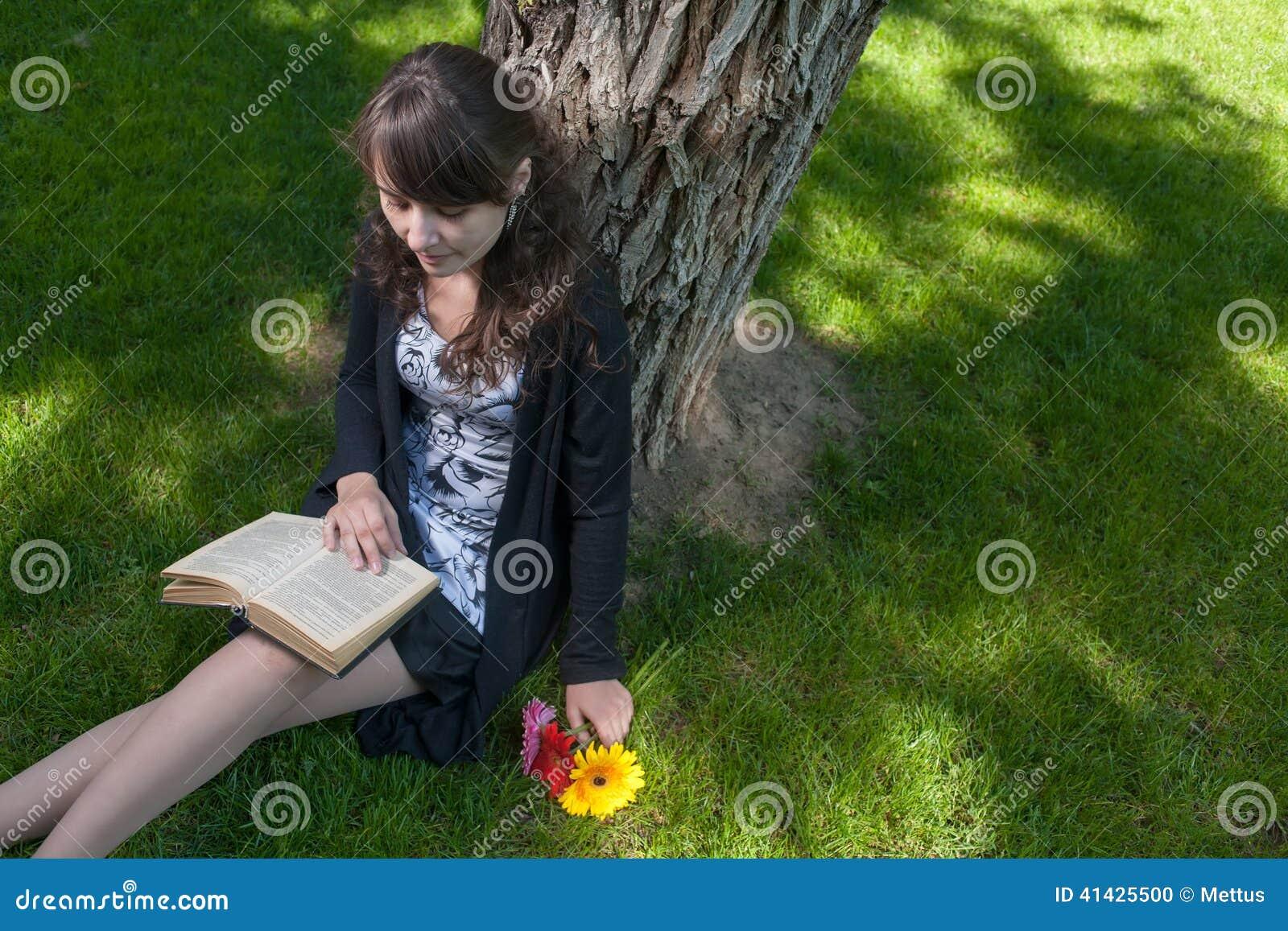 Читать внутри парк Милая прочитанная девушка сидя на траве и старой книге