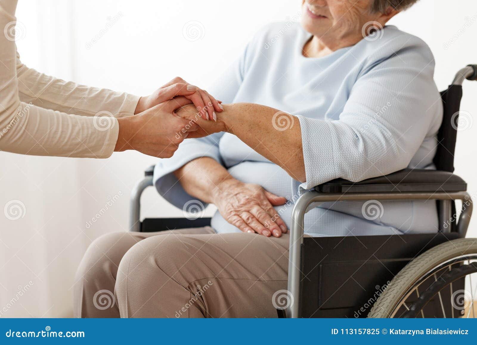 Член семьи поддерживая выведенную из строя бабушку