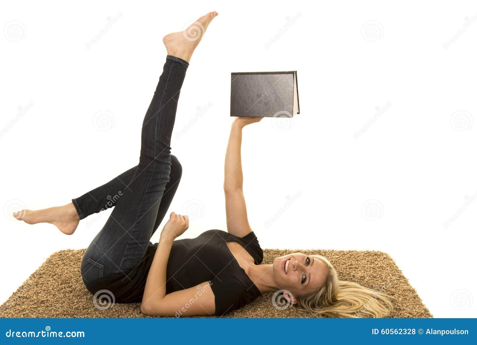 Чтение женщины нося черное положение на задних книге и ногах владением вверх