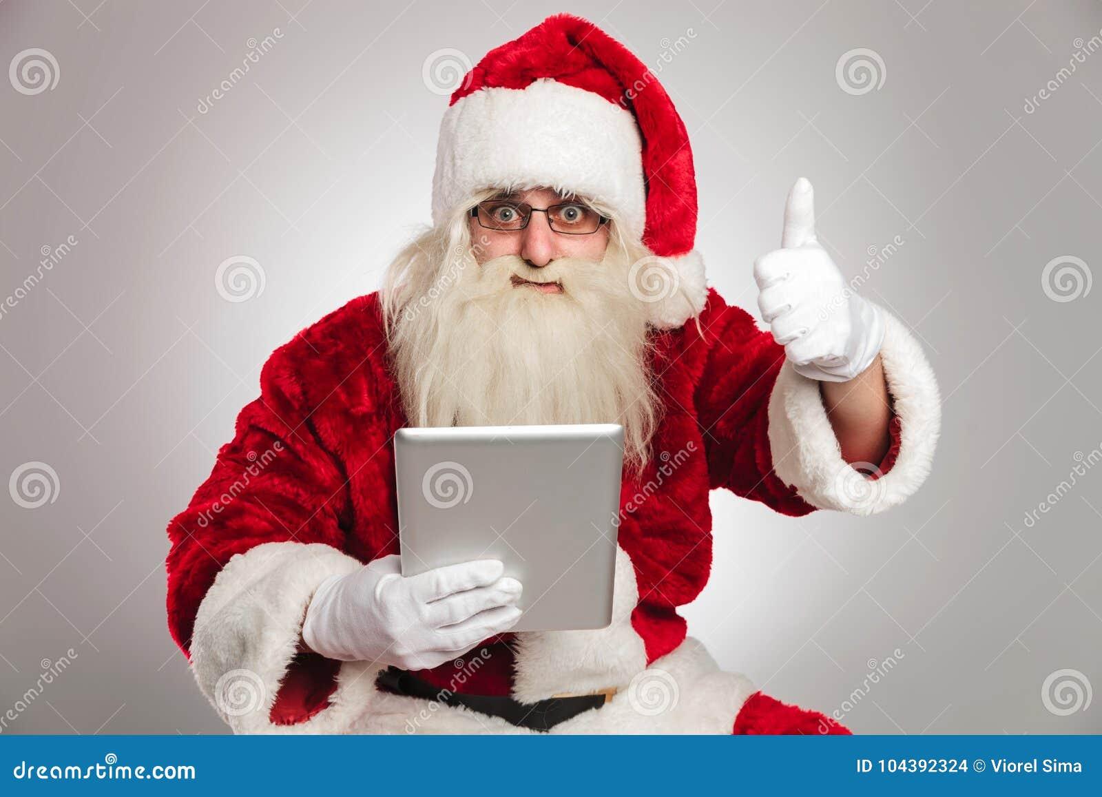 Чтение Санта Клауса на таблетке и делает одобренный знак