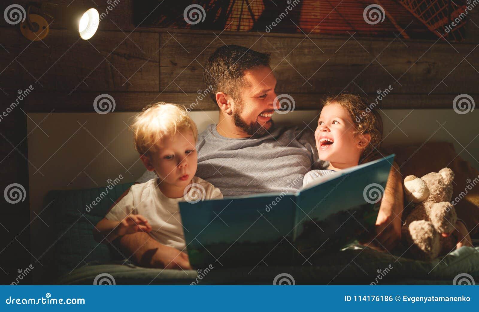 Чтение семьи вечера отец читает детей книга перед goin