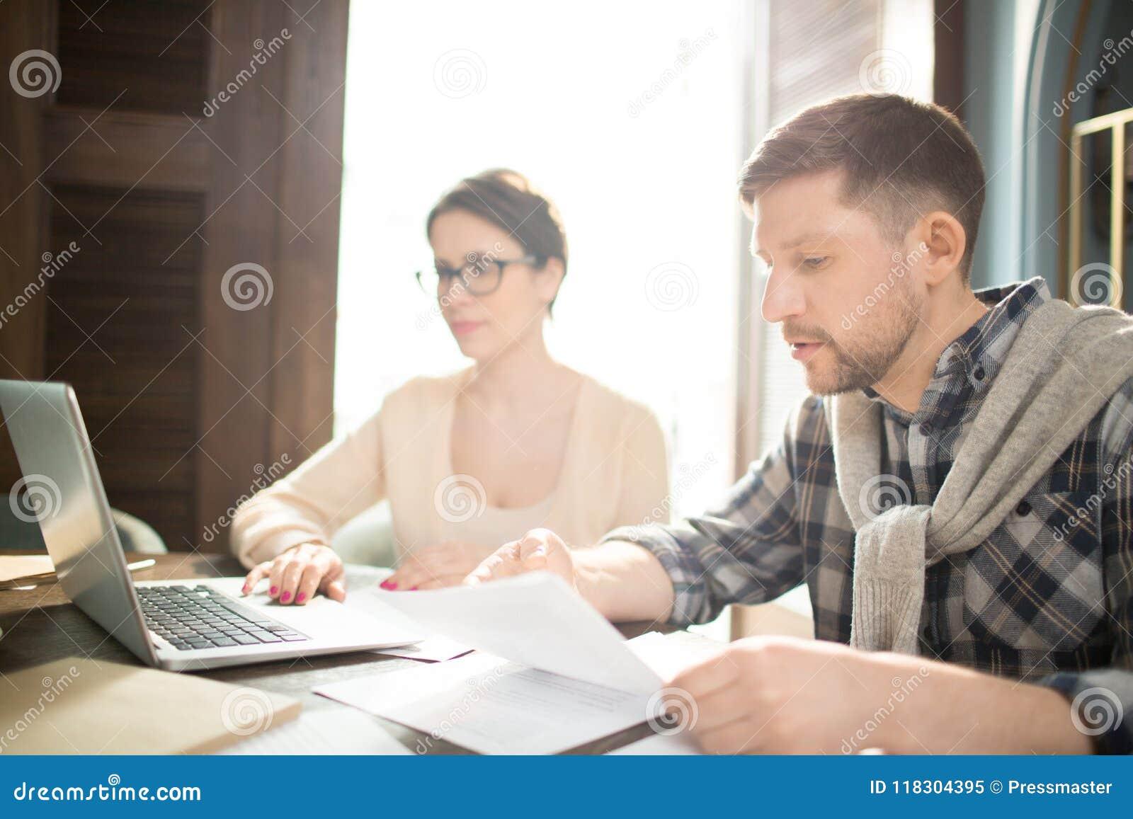 Чтение человека завертывает в бумагу около женщины с компьтер-книжкой