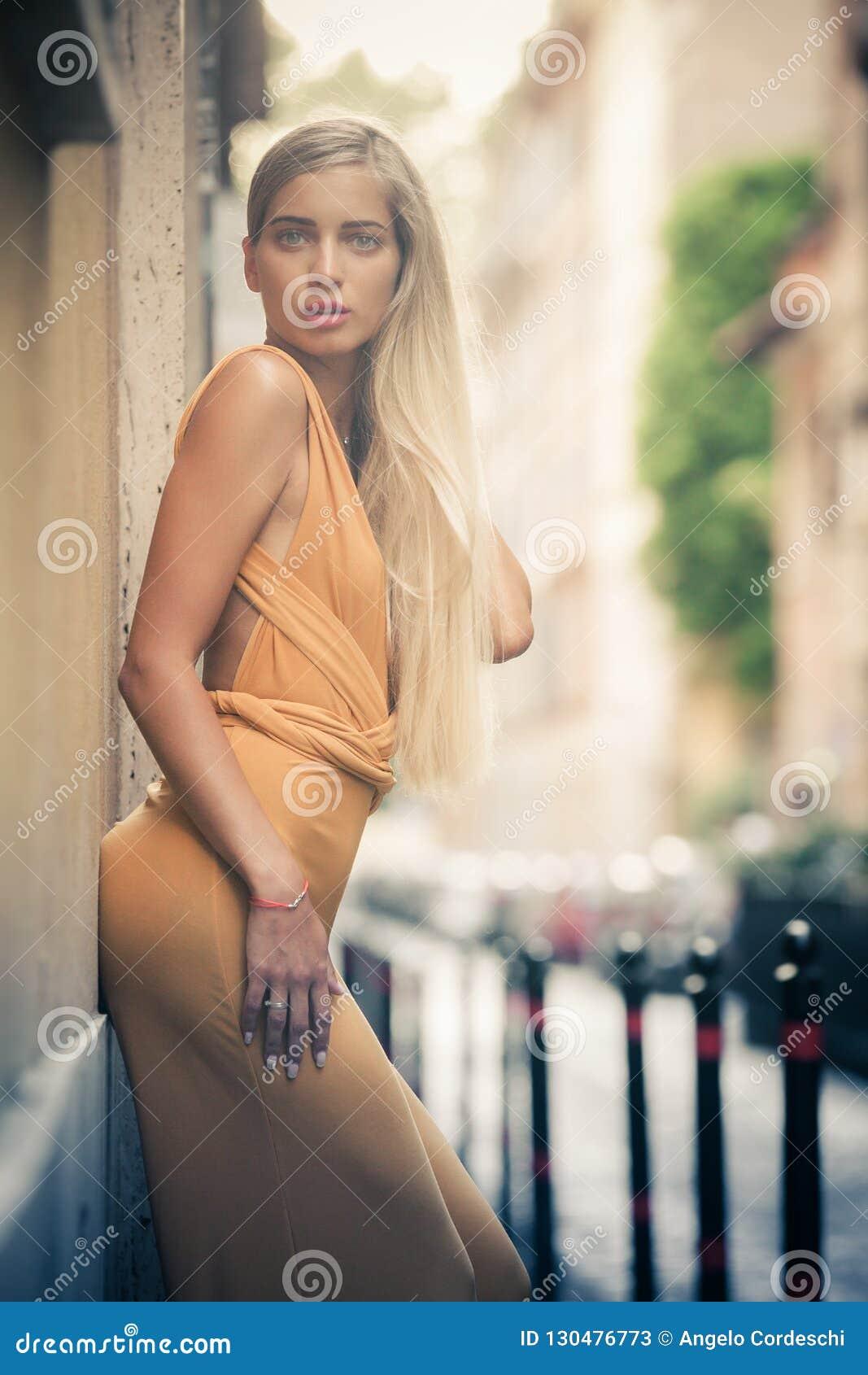 Чувственная и привлекательная молодая белокурая женщина полагаясь против стены на улице в городе