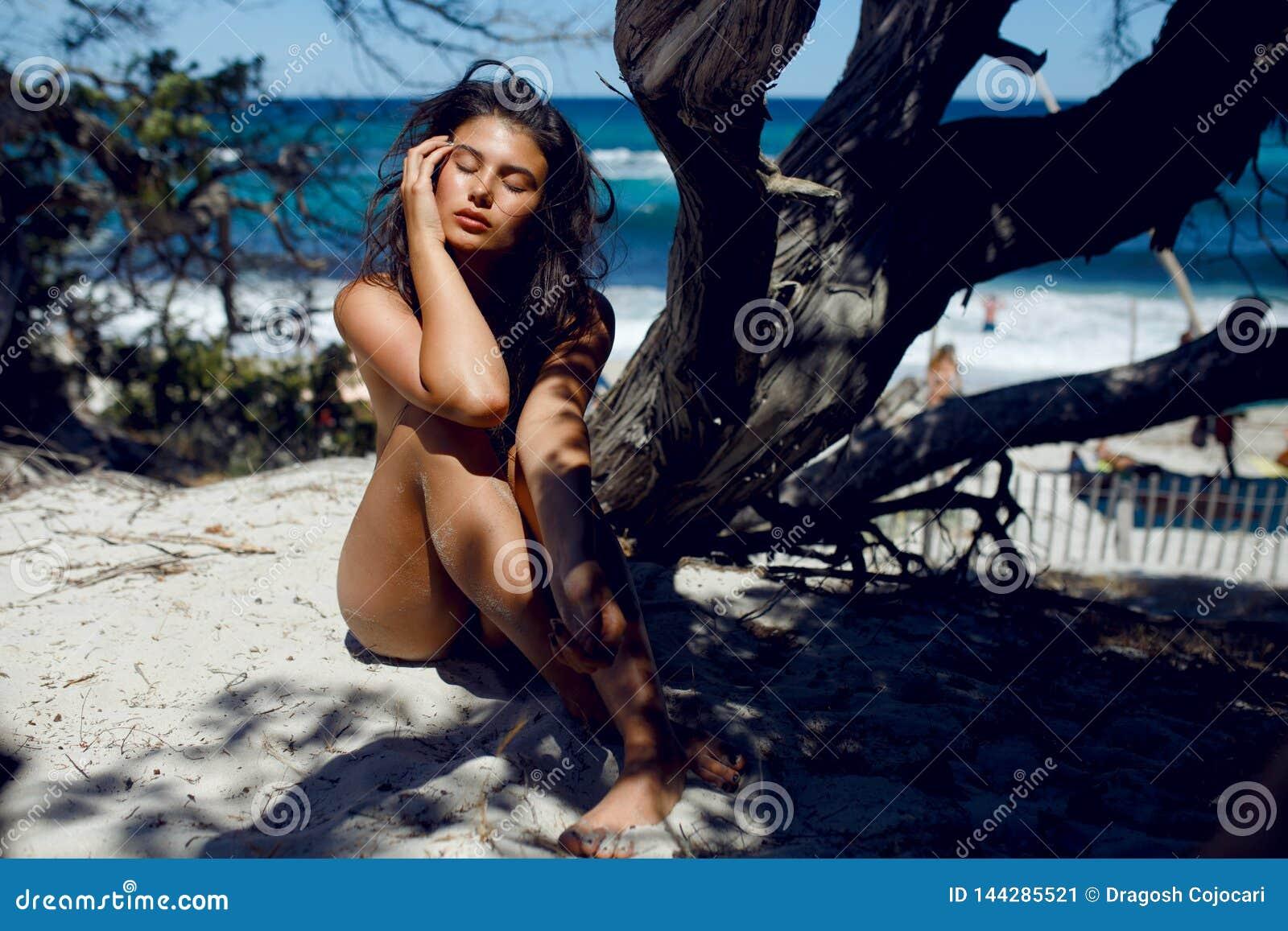 Чувственная молодая женщина с длинными волосами брюнета и закрытыми глазами, представлять нагой на beac, предпосылка seascape
