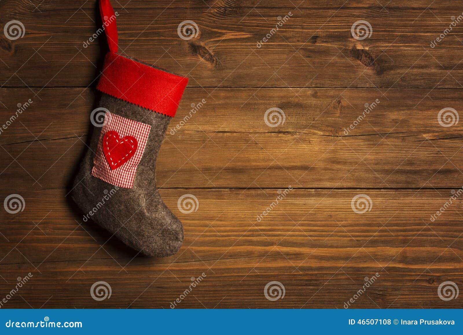 Чулок рождества, носок вися над предпосылкой Grunge деревянной,