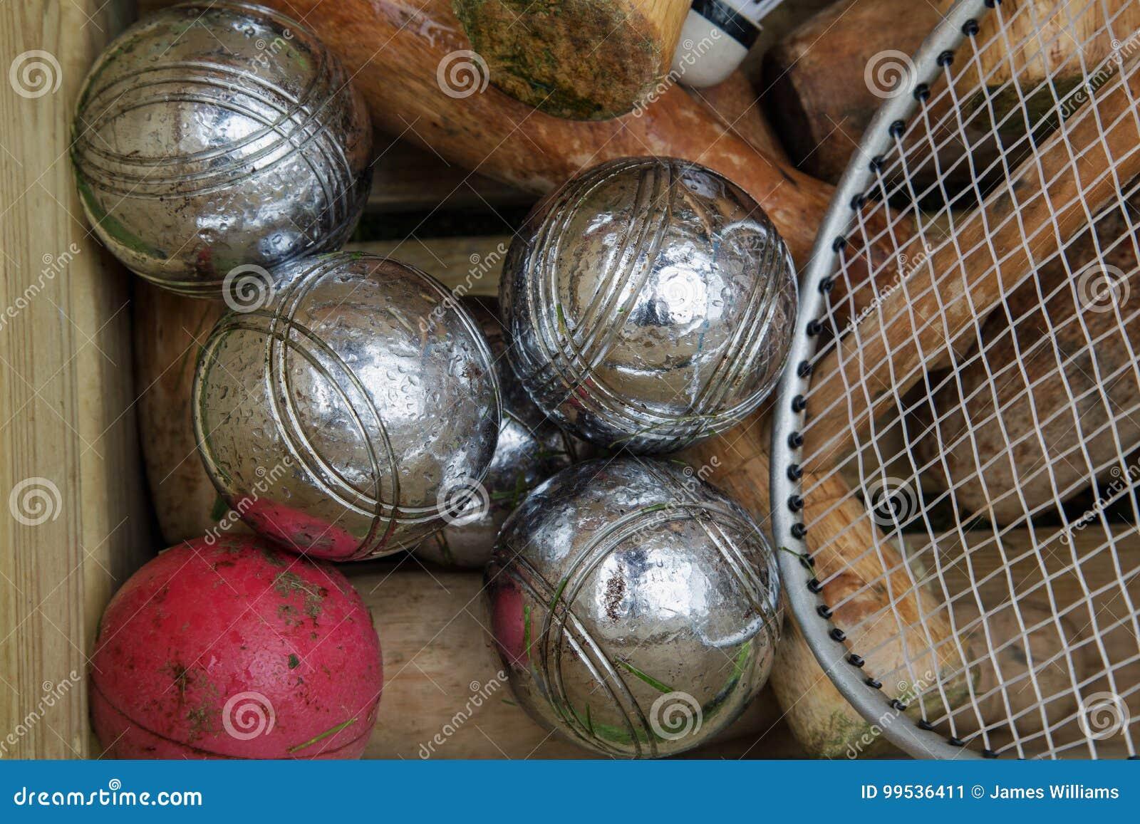 Шарики Boules и мушкелы крокета и ракетки тенниса в коробке осмотренной сверху