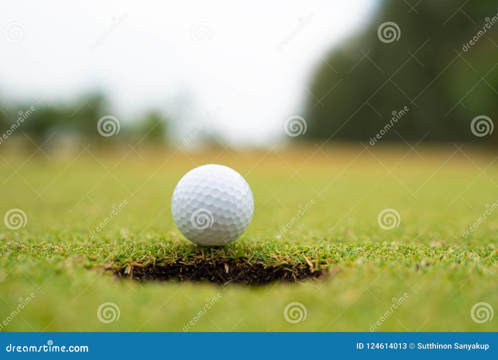 Шар для игры в гольф на губе конца чашки вверх, шар для игры в гольф на лужайке