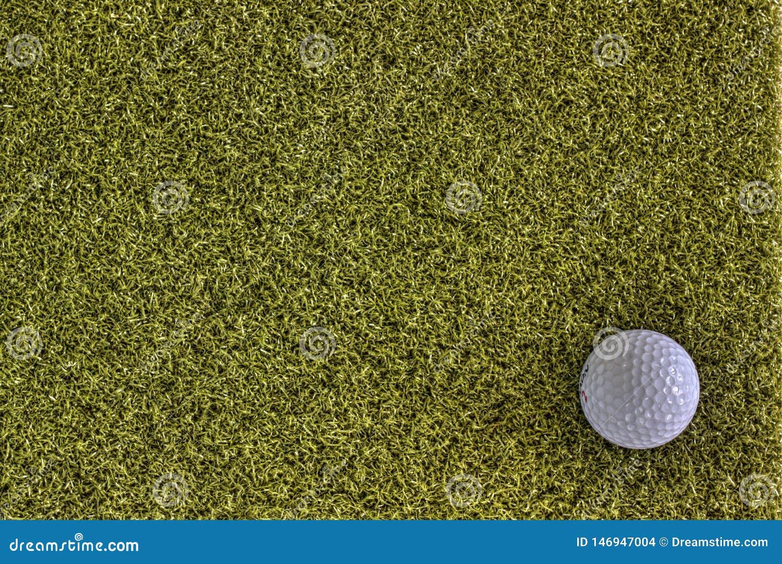 Шар для игры в гольф на зеленой задней земле