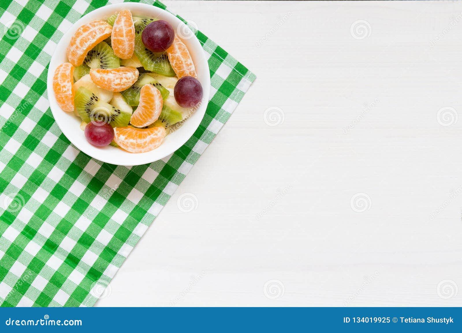 Шар здорового салата свежих фруктов на белой деревянной предпосылке, взгляде сверху, космосе экземпляра