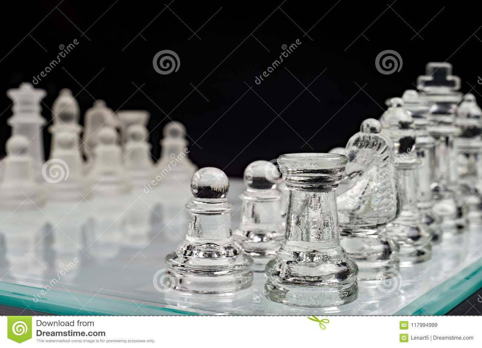 Шахмат, стеклянная доска с пешками на черной предпосылке