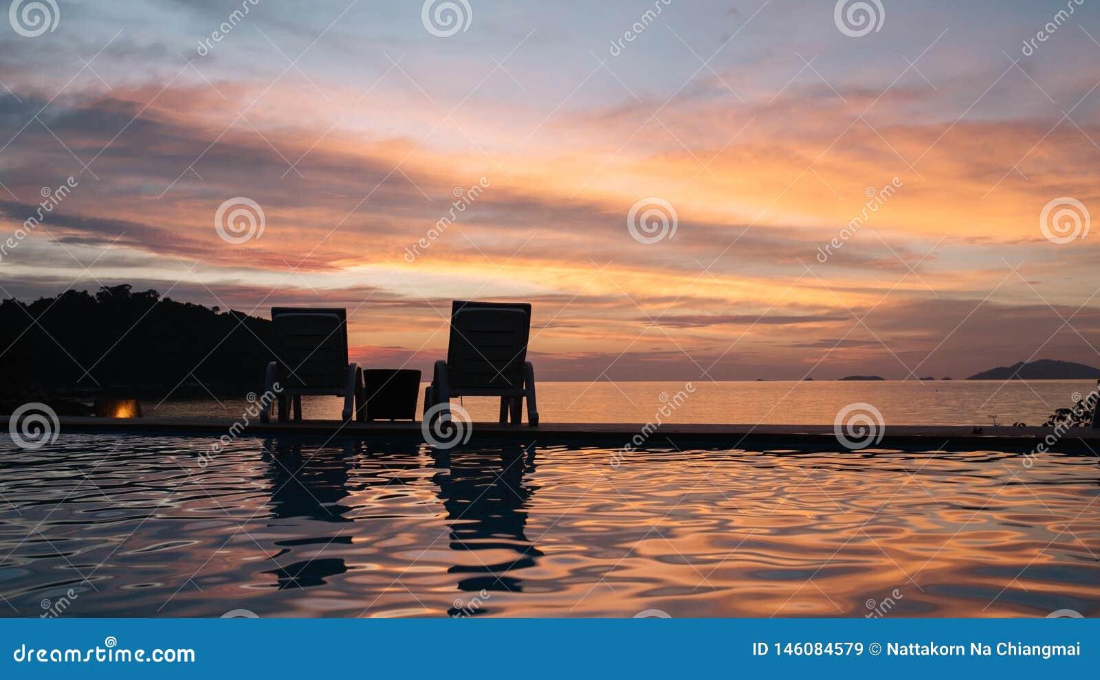 Шезлонг наблюдает заход солнца в вечере летом на Таиланде