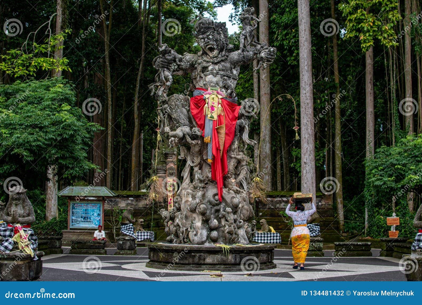 Шествие красивых балийских женщин в традиционных костюмах - саронг, идя к индусской церемонии около большого памятника демона