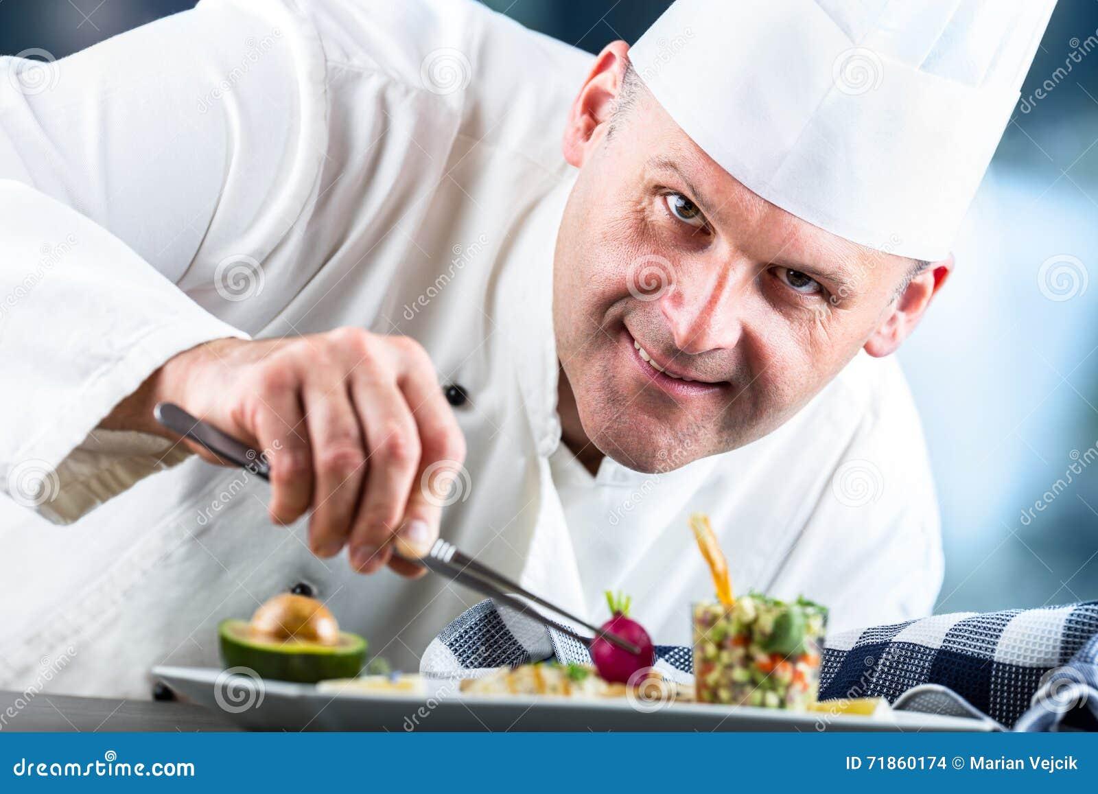 Шеф-повар Варить шеф-повара Шеф-повар украшая блюдо Шеф-повар подготавливая еду Шеф-повар в кухне гостиницы или ресторана подгота
