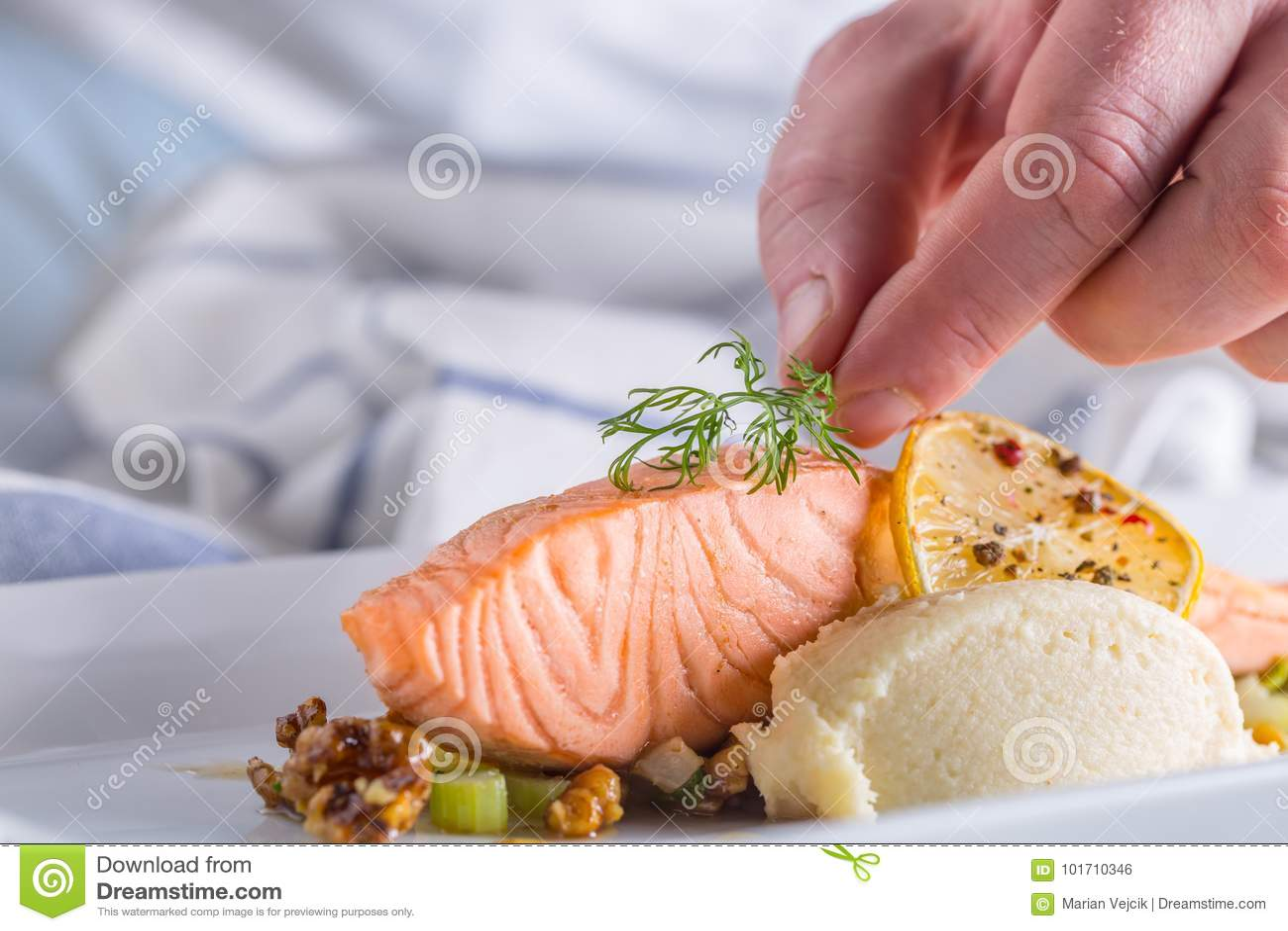 Шеф-повар в кухне гостиницы или ресторана варя, только руки Подготовленный salmon стейк с украшением укропа