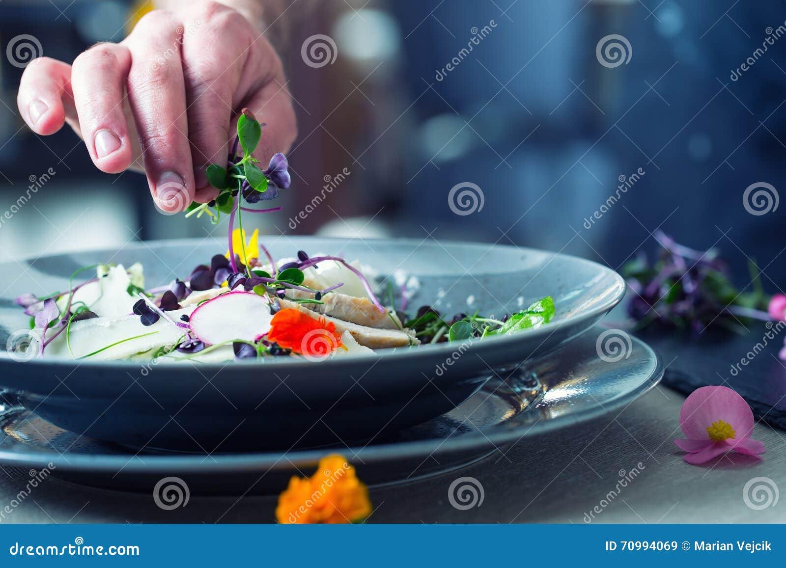 Шеф-повар в кухне гостиницы или ресторана варя, только руки Он работает на микро- украшении травы подготовлять овощ салата