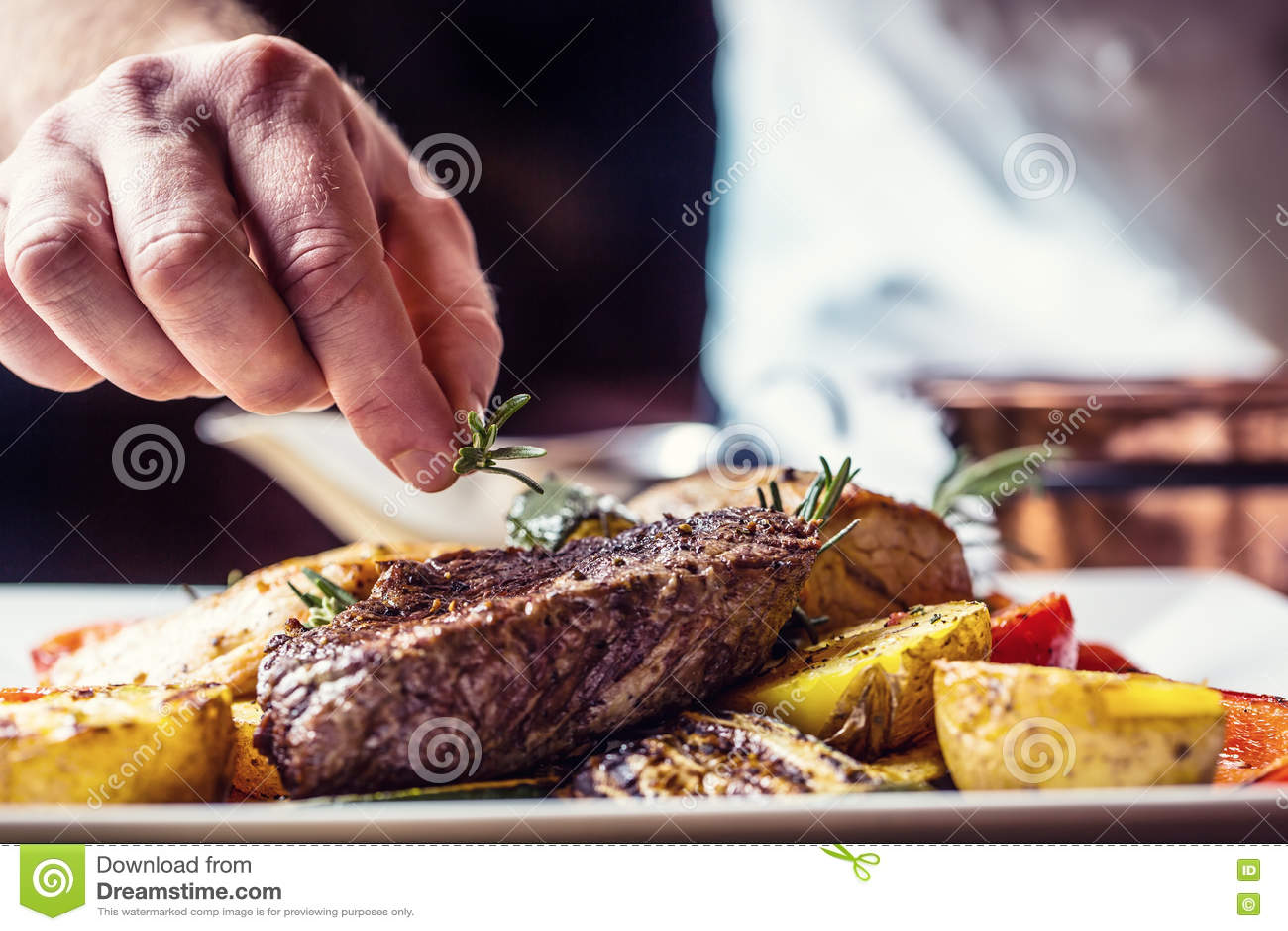 Шеф-повар в кухне гостиницы или ресторана варя только руки Подготовленный стейк говядины с vegetable украшением