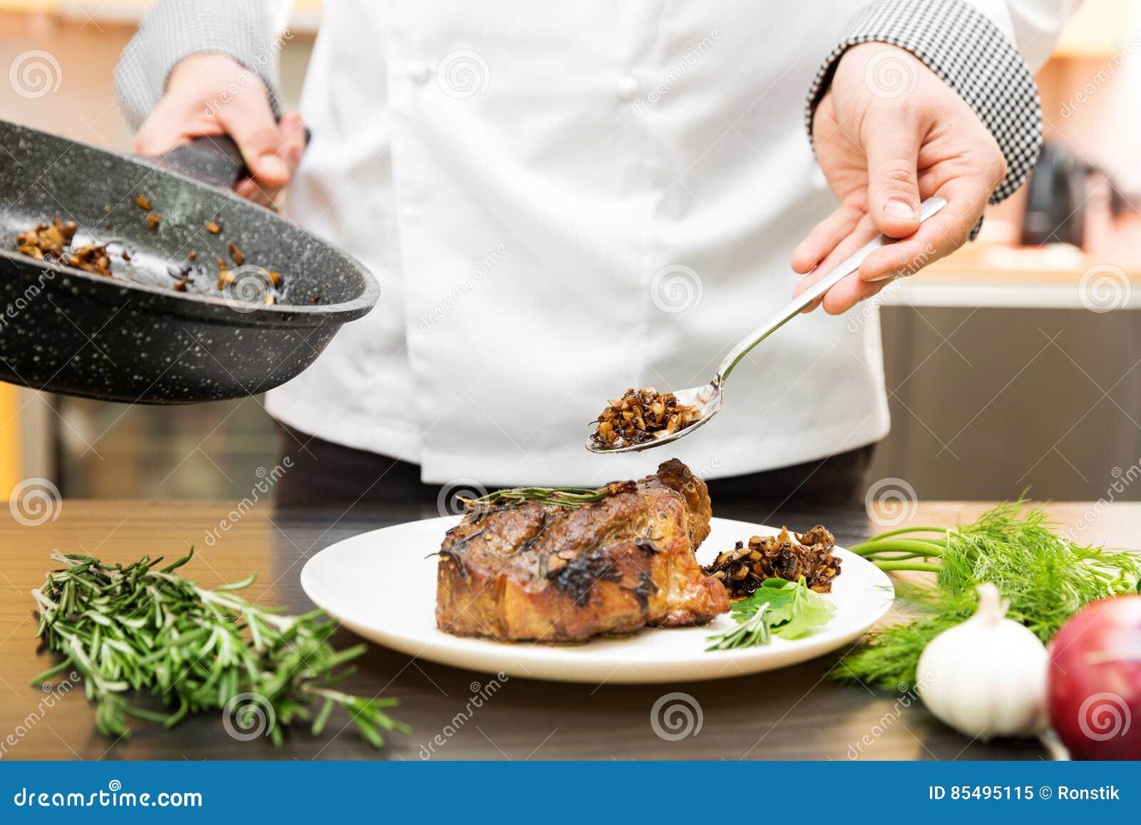 Шеф-повар украшая зажаренное в духовке мясо с соусом гриба