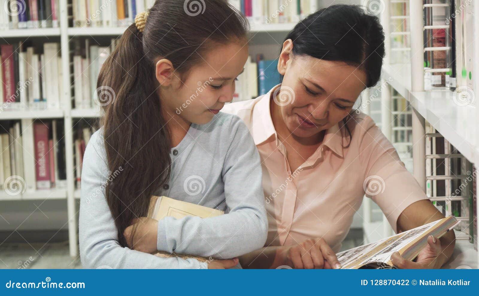 Шикарная счастливая зрелая женщина читая книгу к ее маленькой дочери