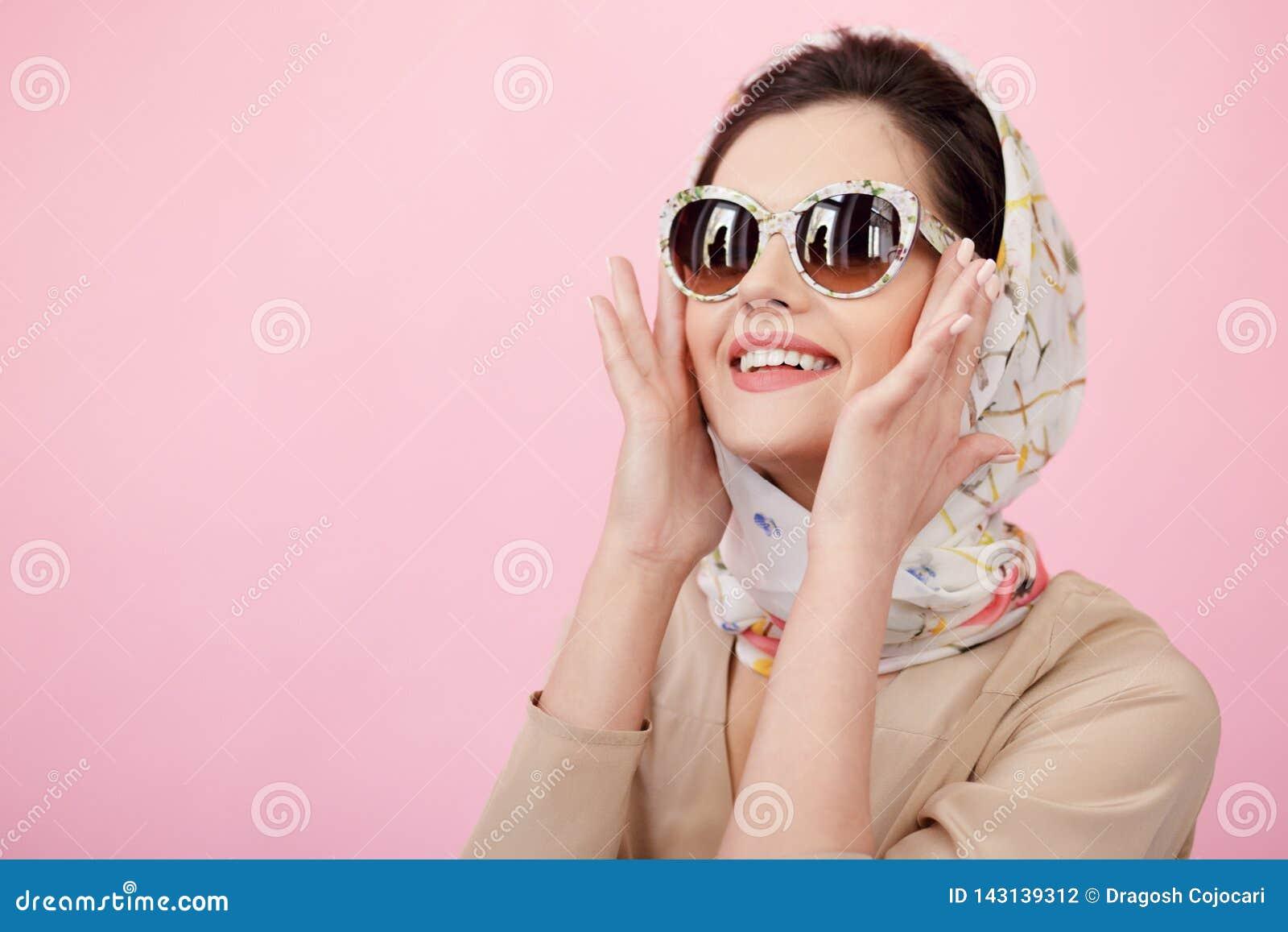 Шикарный стиль молодой женщины одел элегантную одежду, представлять чувственный в студии, изолированной на розовой предпосылке