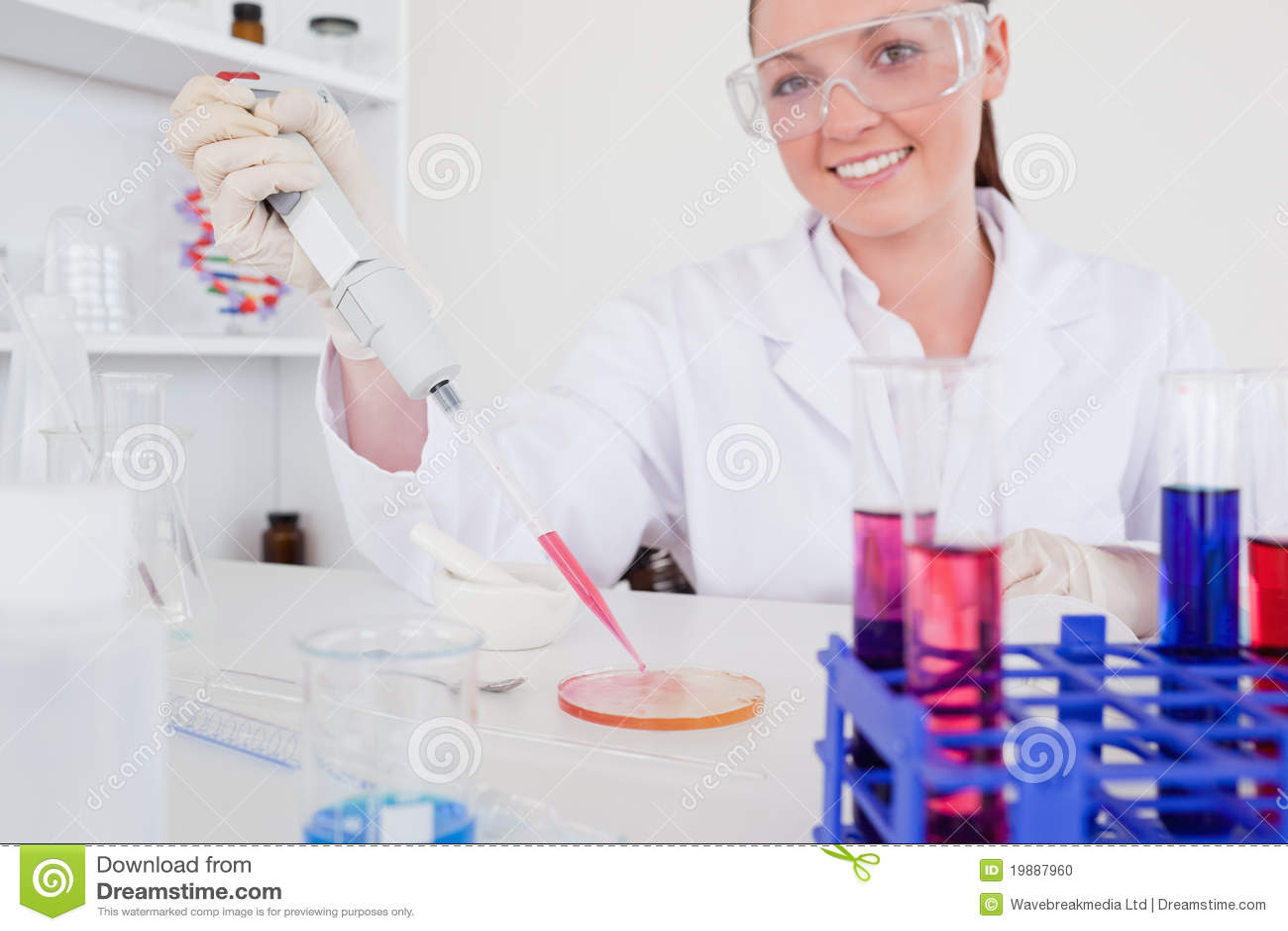 Шикарный red-haired научный работник используя пипетку