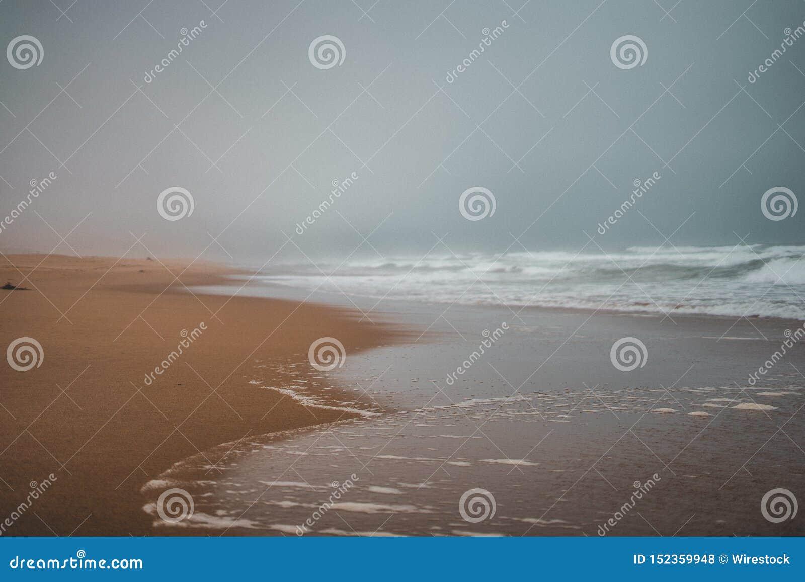 Широкая съемка пляжа с сильными броскими волнами получая более близко