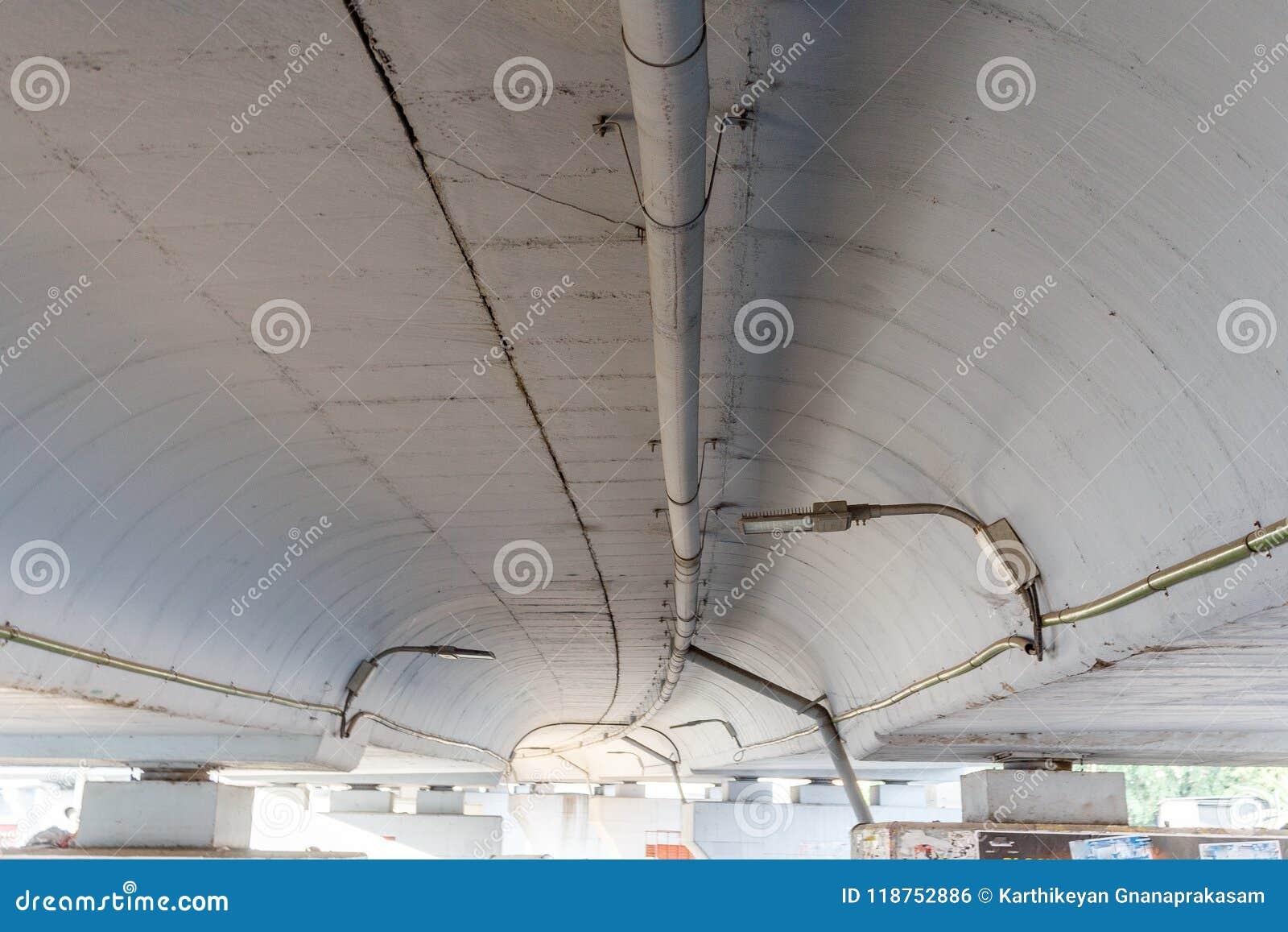Широкий взгляд подполья эстакады увиденной с светами лампы и