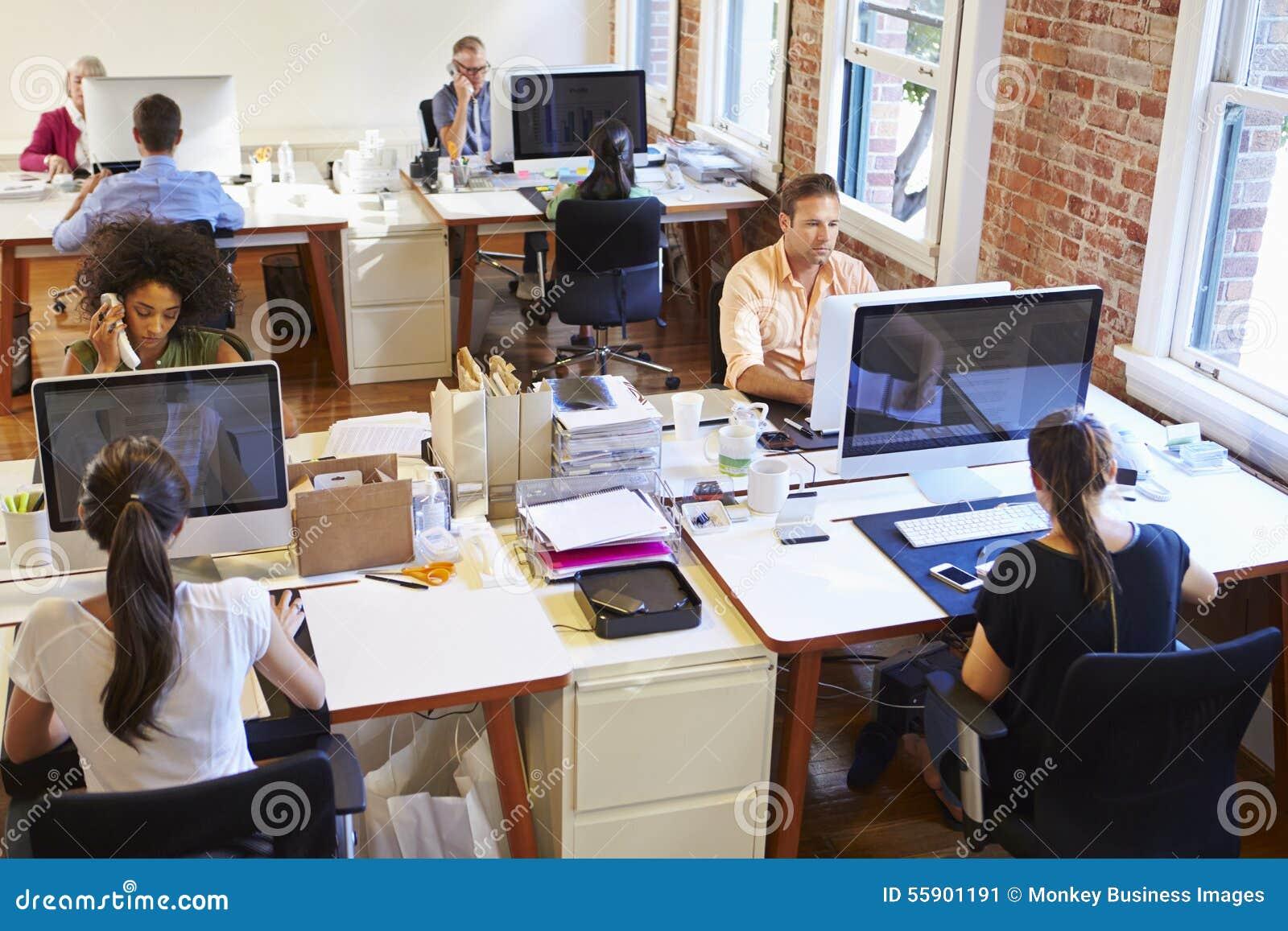 Широкоформатный взгляд занятого офиса дизайна с работниками на столах