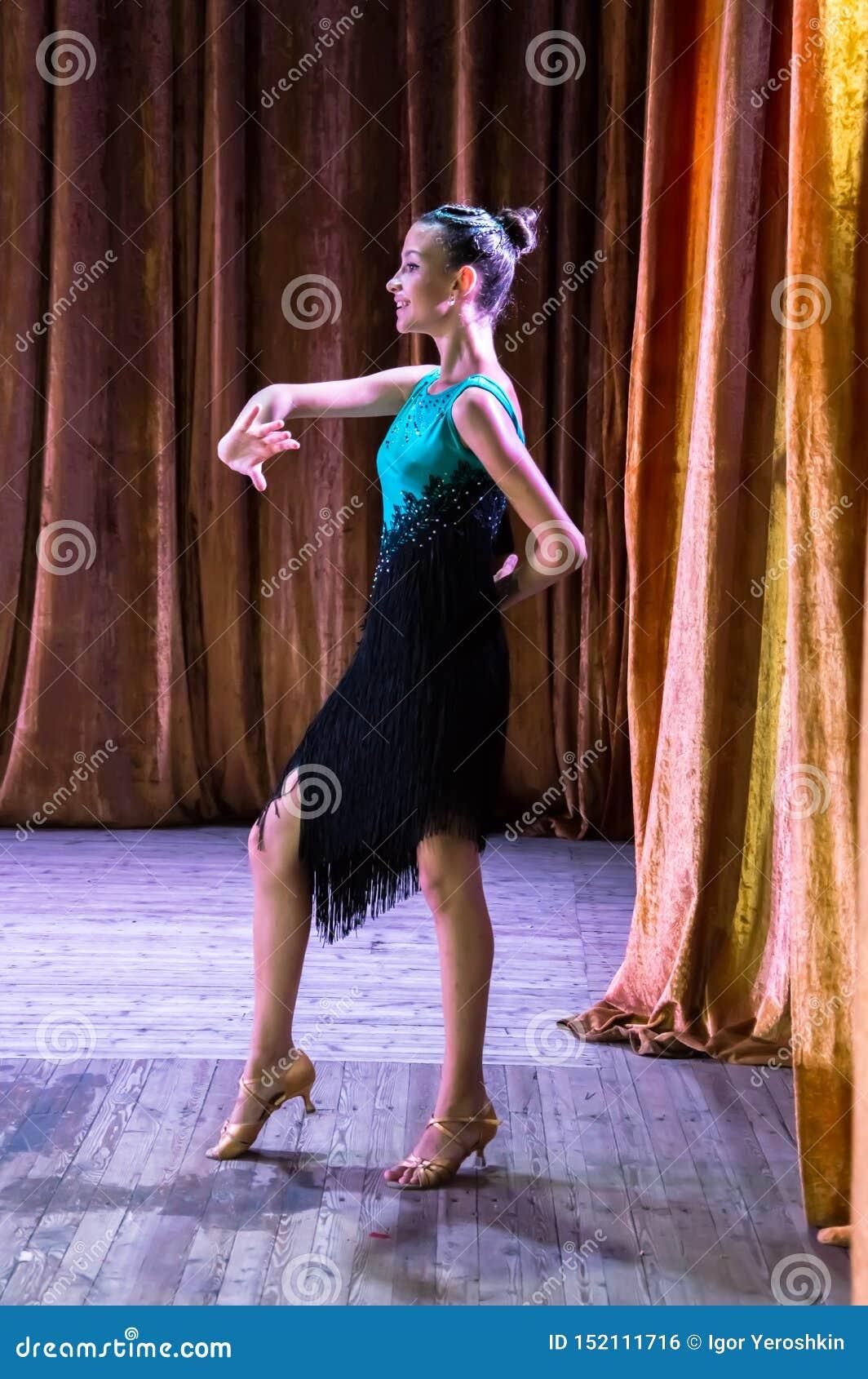 Школа танцев Зрачки принимают экзамены Мальчики и девушки в красивых костюмах танца на этапе