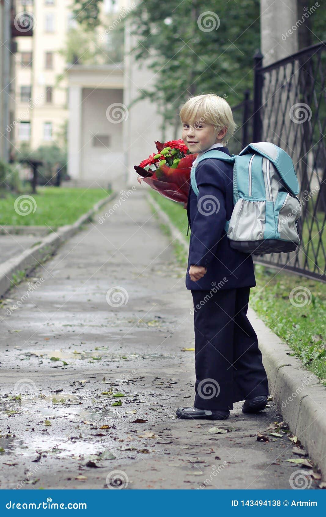 Школьник на его пути в школу Мальчик идя к первому классу в его школе на пути Дети и образование в городе