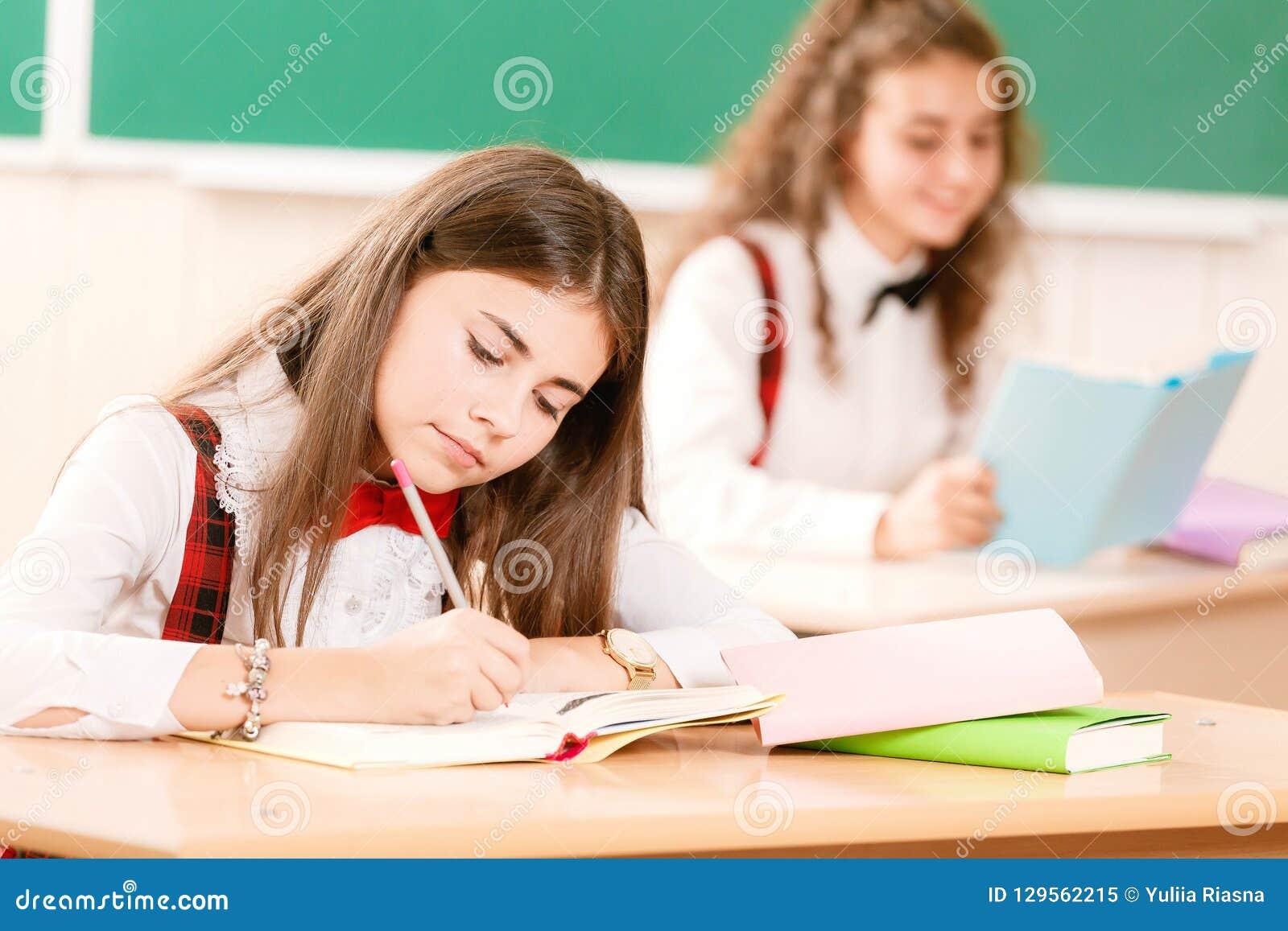 Школьницы в школьных формах сидят для пар в классе Девушки идут к школе