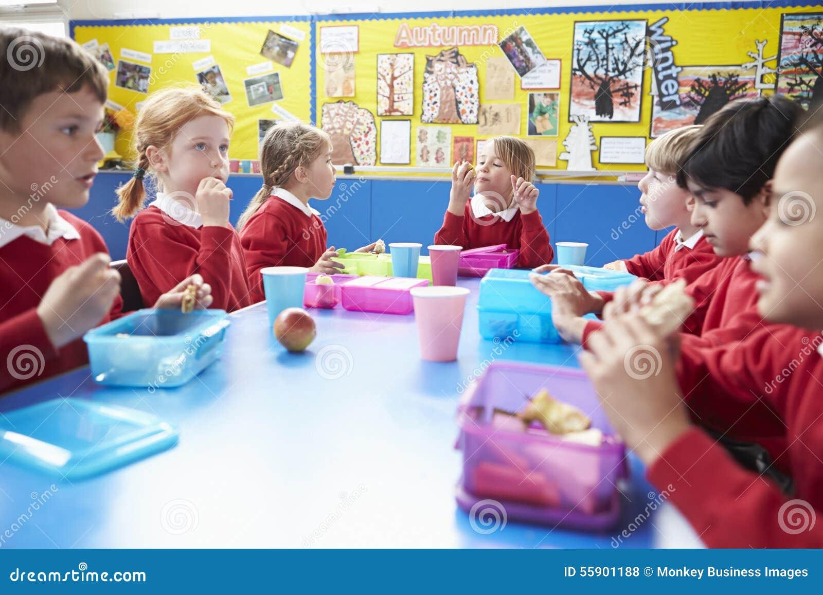 Школьники сидя на таблице есть упакованный обед