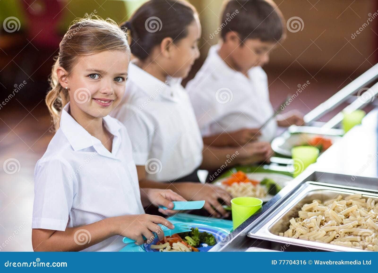 Школьница при одноклассник стоя близко счетчик буфета
